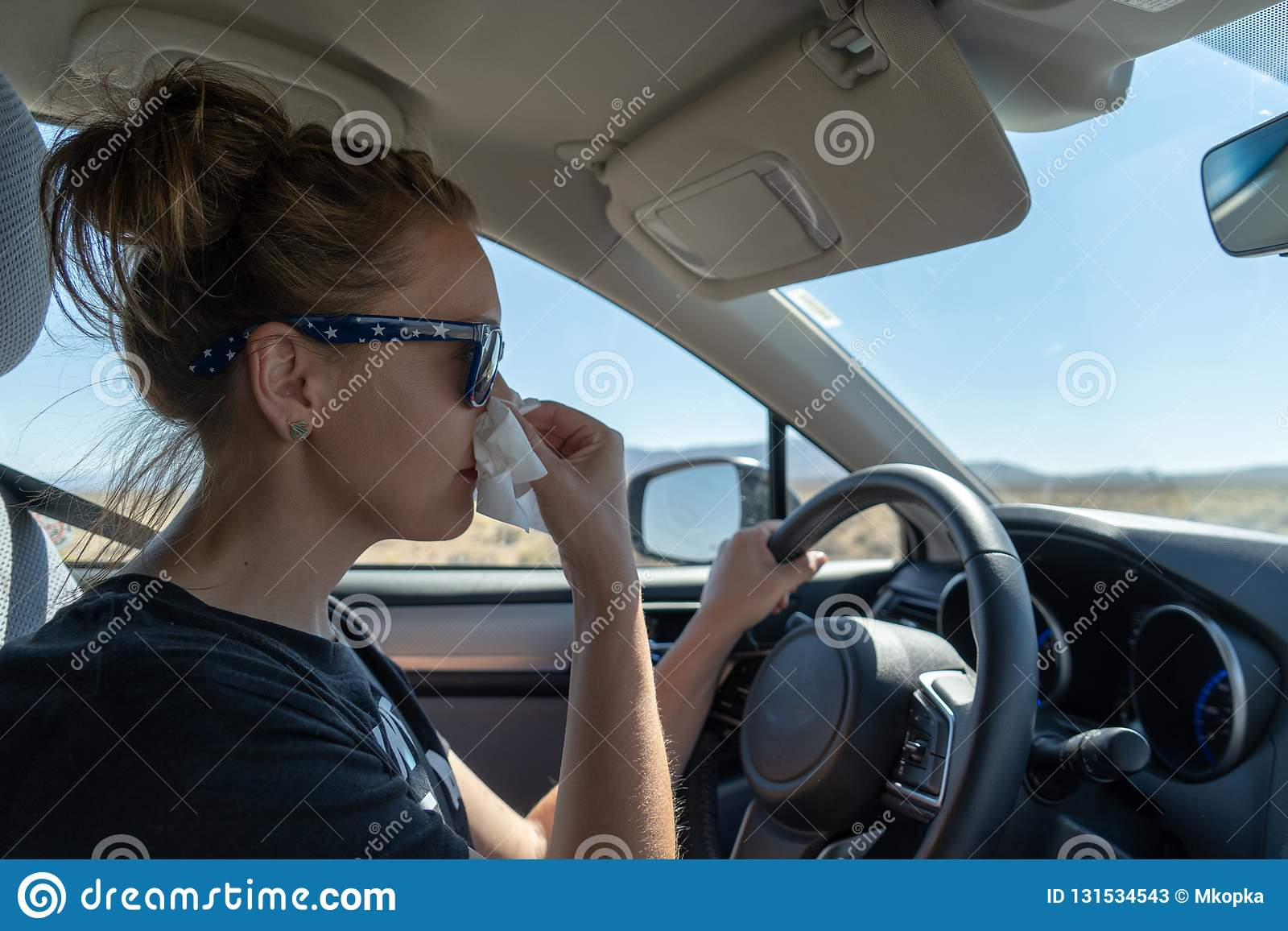 O motorista fêmea da mulher usa um tecido para fundir seu nariz ao conduzir Conceito para a condução confundida, multi encarregar