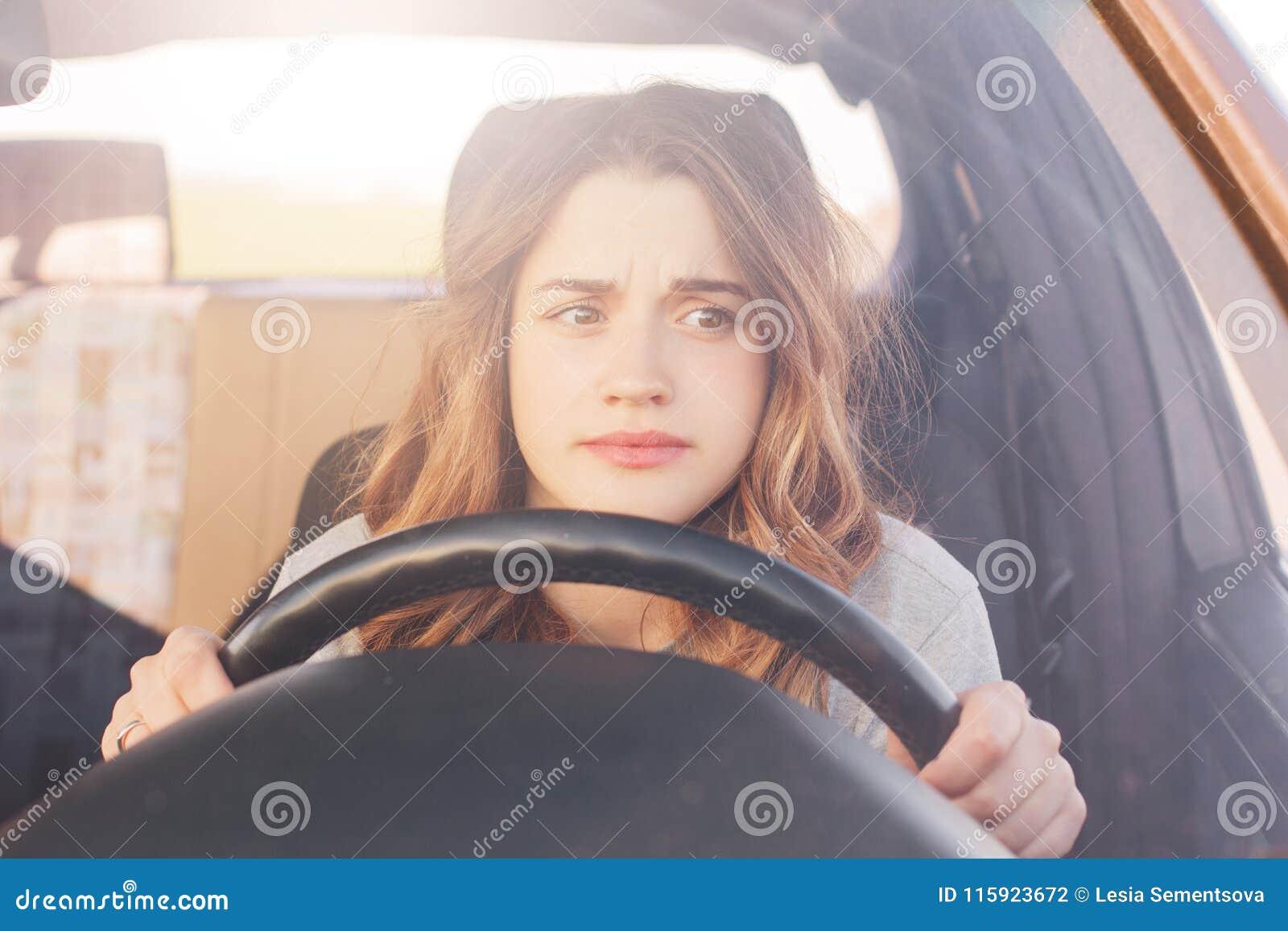 O motorista fêmea nervoso senta-se na roda, preocupou a expressão como afraids para conduzir só o carro pela primeira vez Mulher