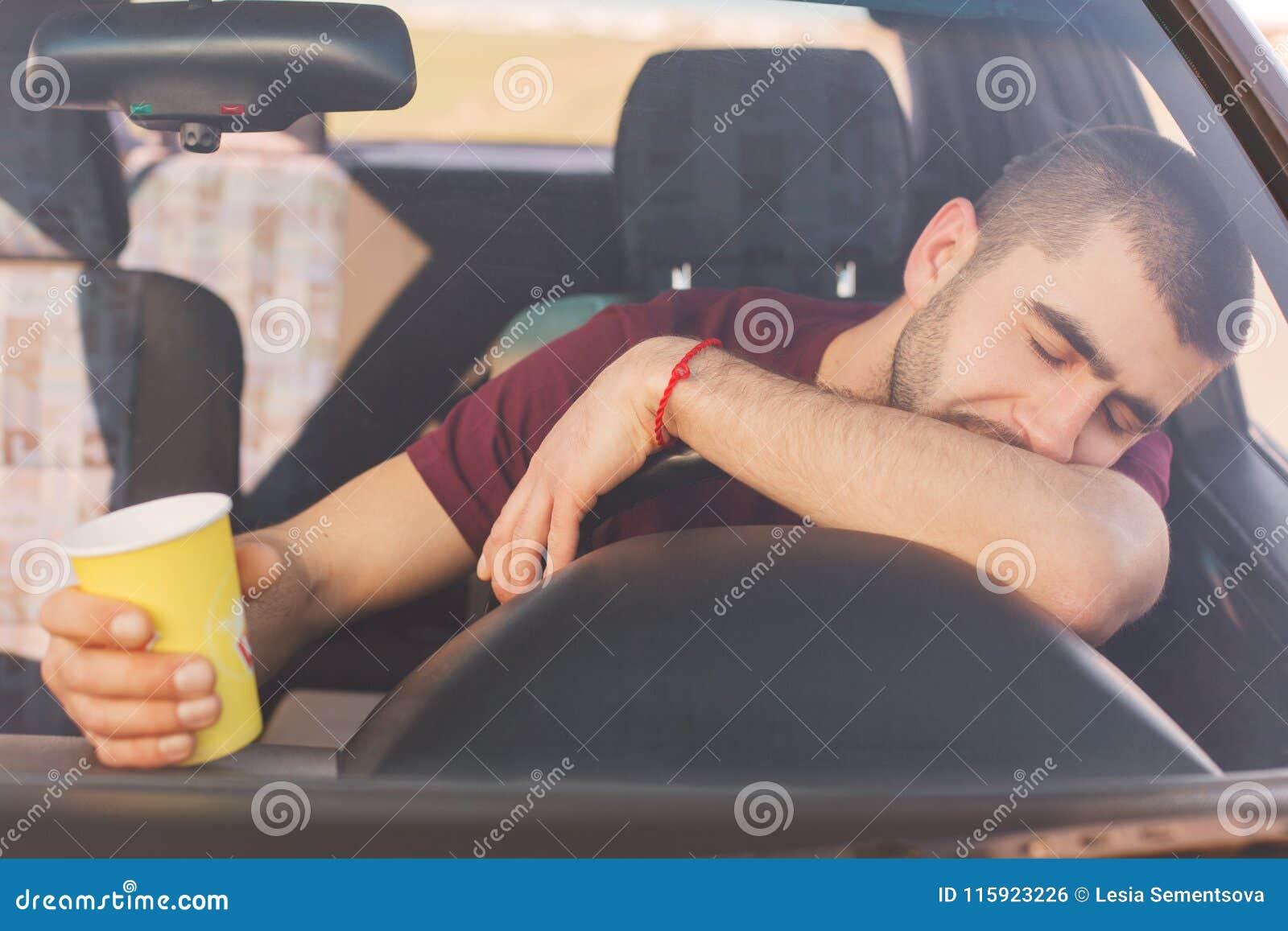 O motorista masculino cansado sobrecarregado fadiga tem a viagem longa no carro, faz a parada para ter o resto, tem a sesta no le
