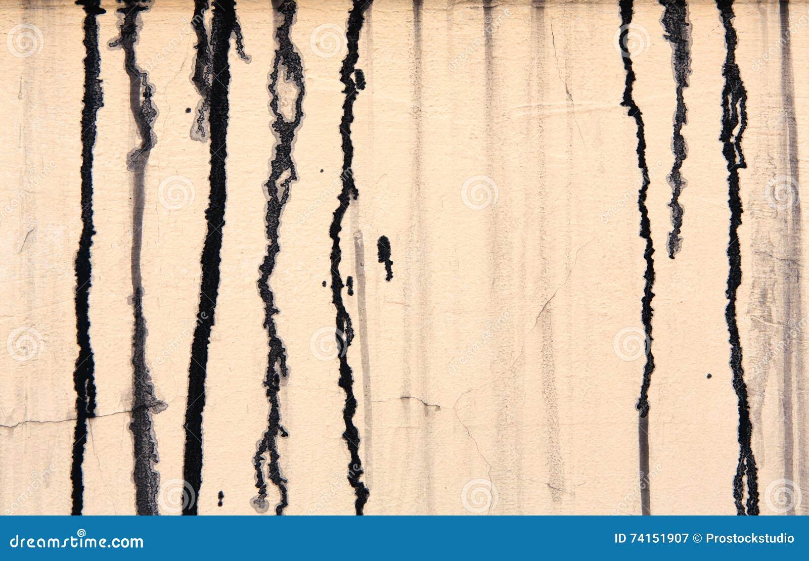 O muro de cimento bege com pintura preta goteja, fundo abstrato