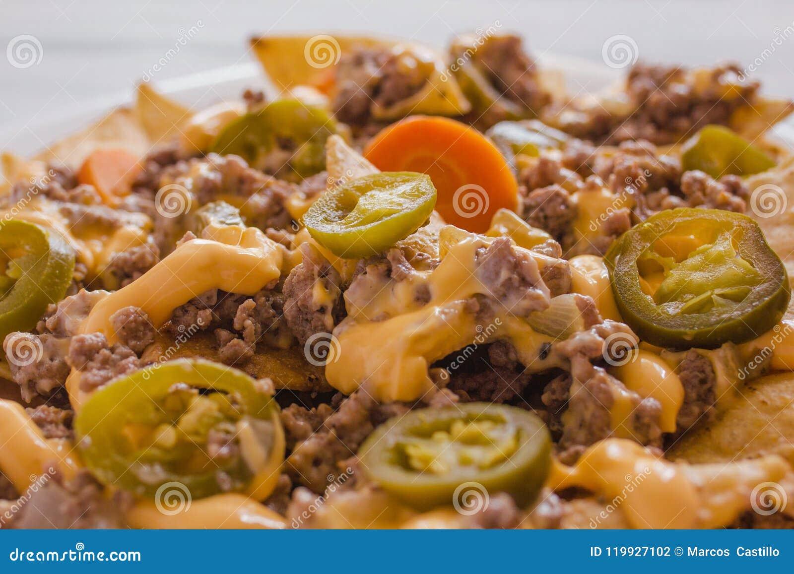 O Nacho lasca o milho decorado com carne picada, queijo derretido, alimento picante mexicano das pimentas dos jalapeños em Méxic
