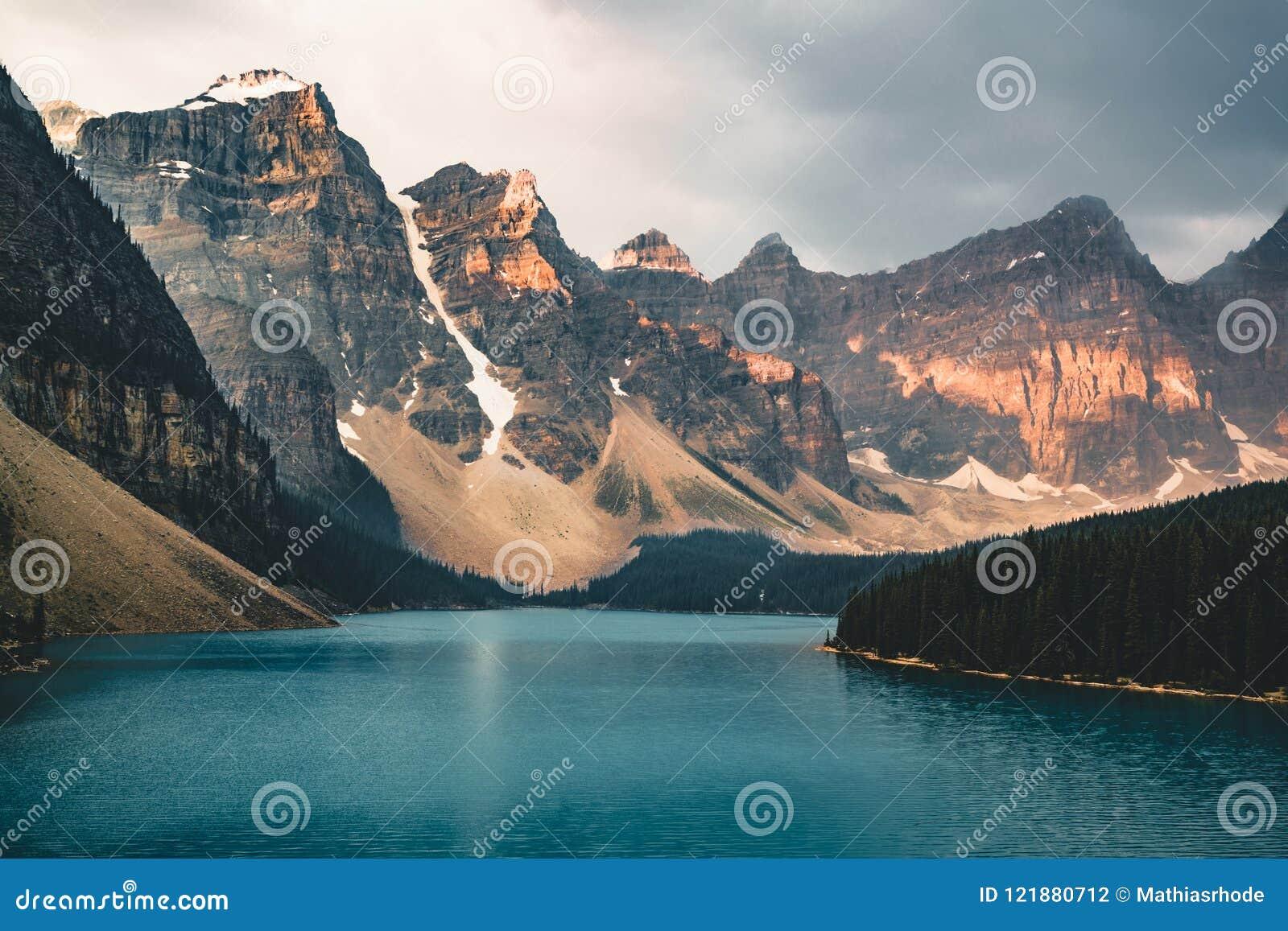 O nascer do sol com águas de turquesa do lago moraine com pecado iluminou montanhas rochosas no parque nacional de Banff de Canad