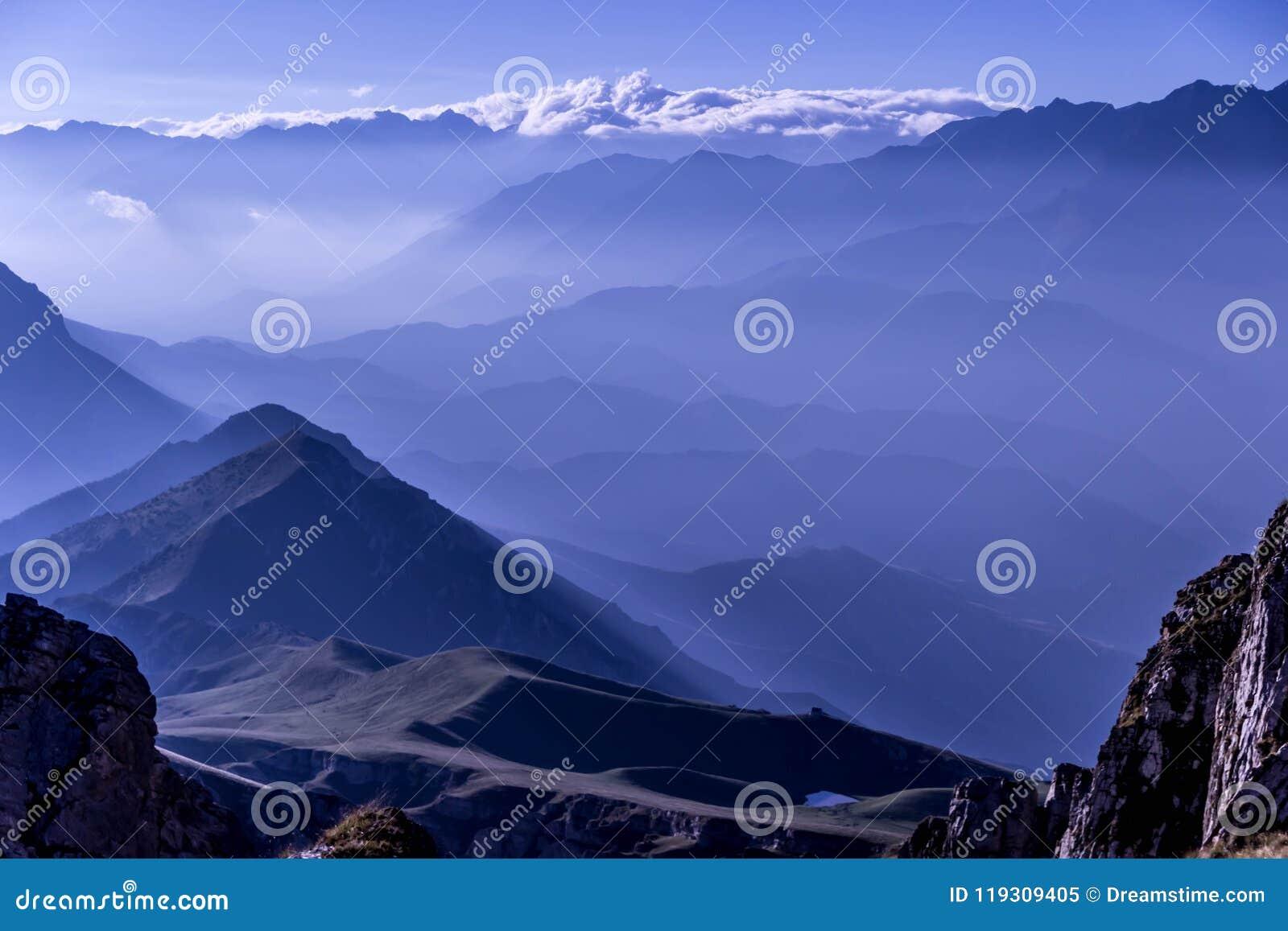 O nascer do sol maravilhoso da manhã de Earlu ilumina-se nas montanhas