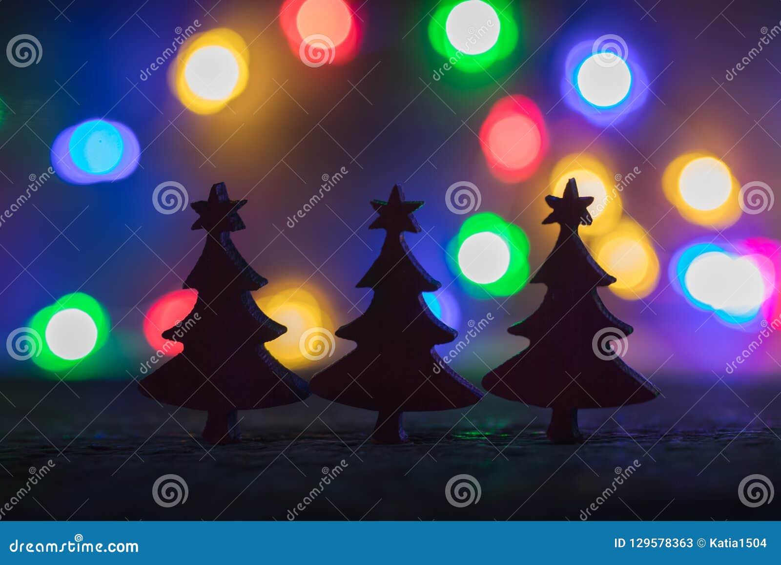 O Natal borrou abeto da silhueta com fundo das luzes da festão, foco seletivo
