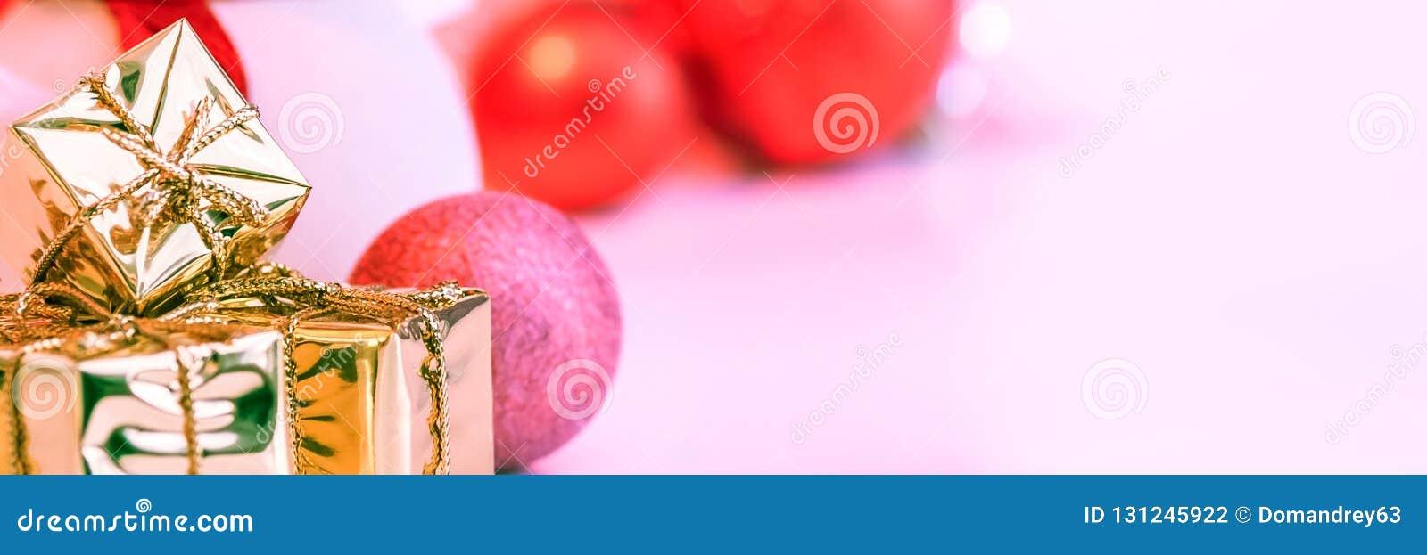 O Natal feliz, ano novo, presentes em umas caixas do ouro, bolas vermelhas do Natal é empilhado no canto esquerdo O fundo é cor-d