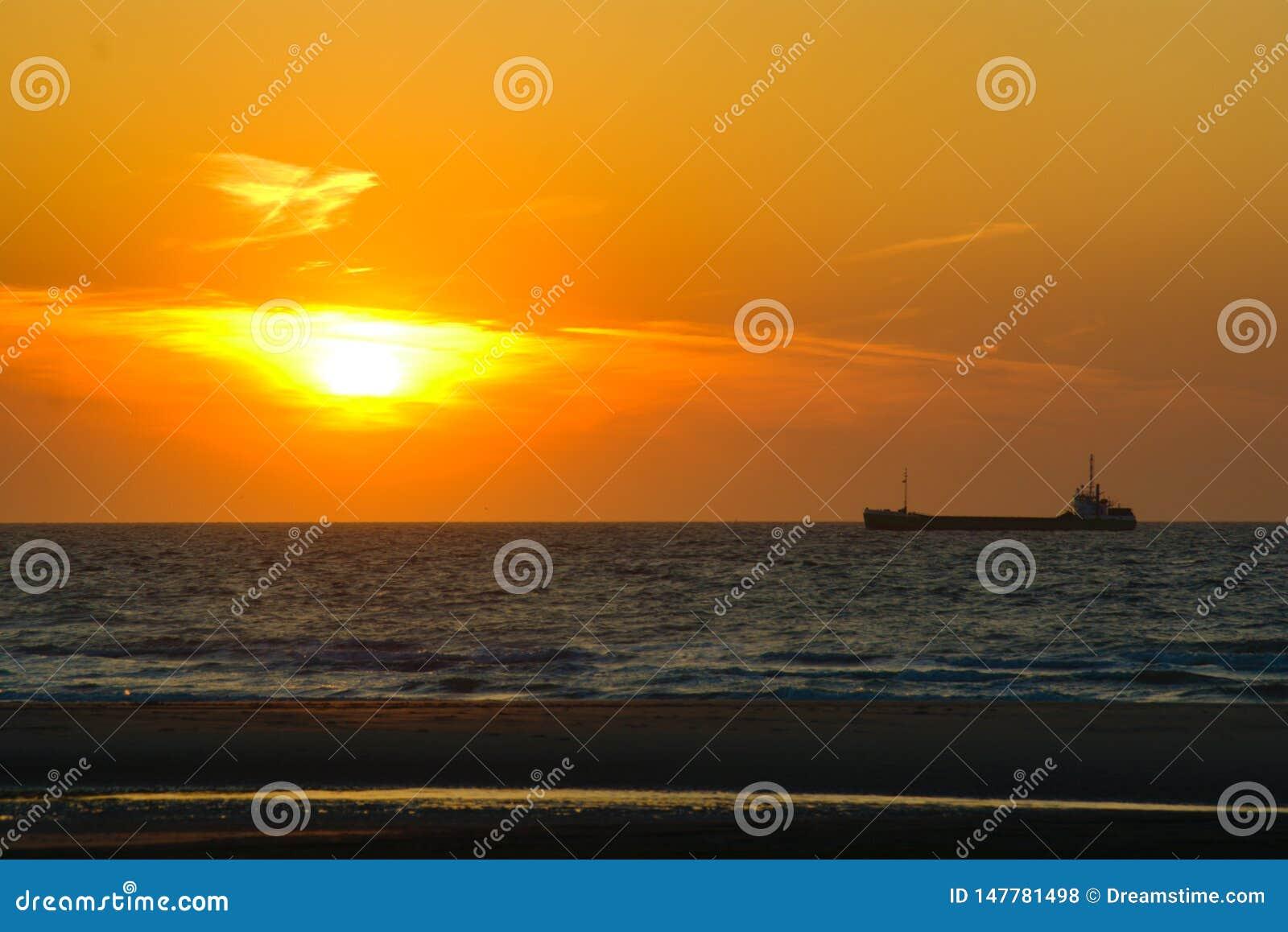 O navio de carga retorna para mover durante o por do sol