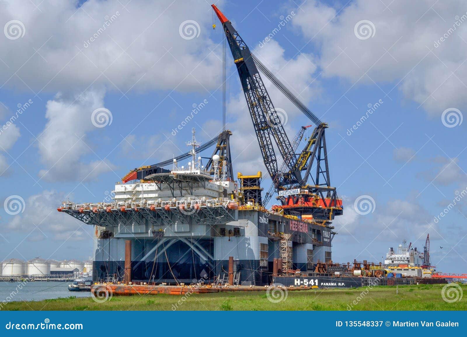 O navio do guindaste de Thialf, uma grande embarcação da construção da água profunda de Heerema amarrou no porto