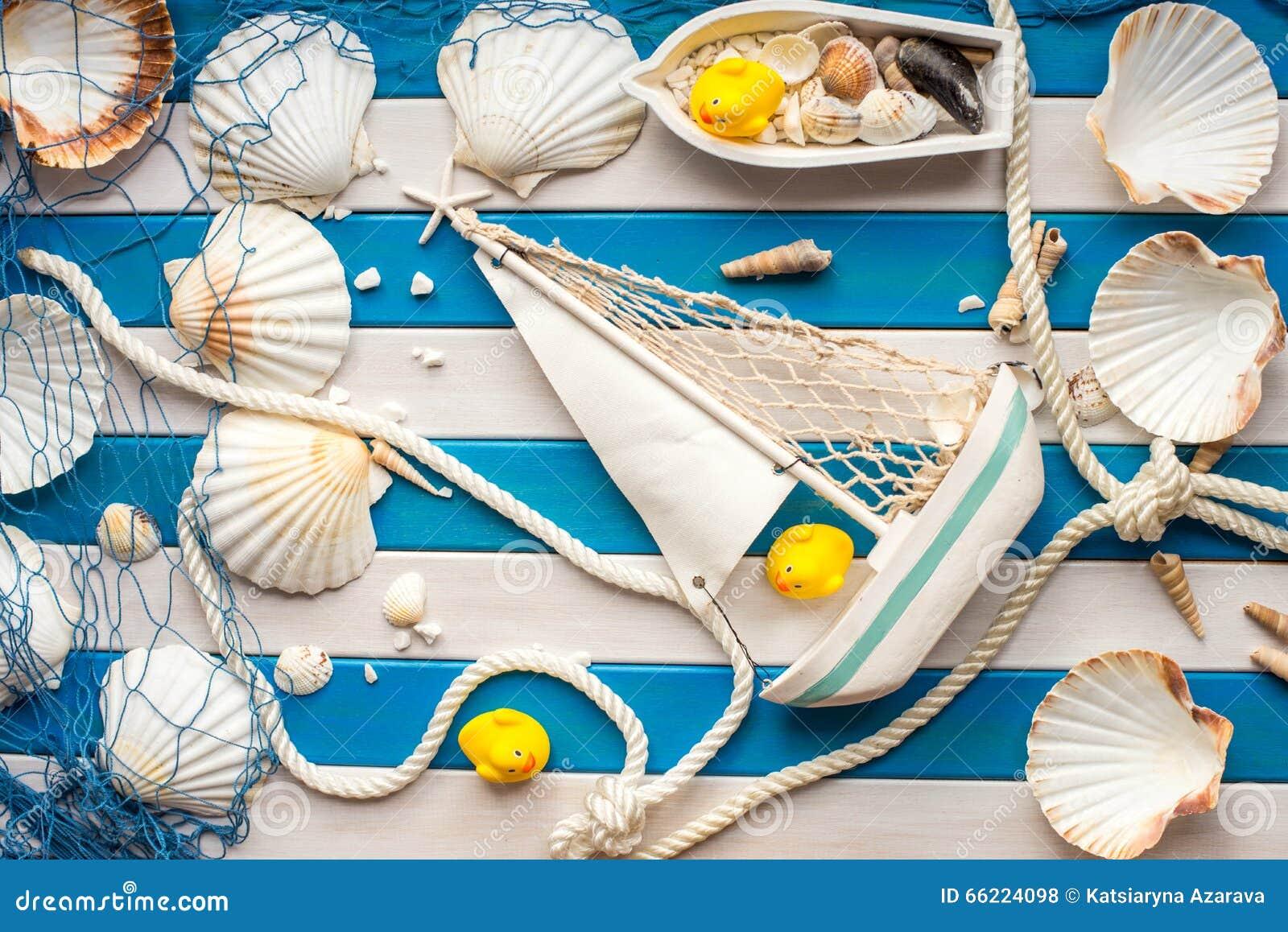 O navio pequeno, o barco de pesca, os shell e o marinheiro rope em um fundo de madeira Conceito do mar Pato de borracha amarelo