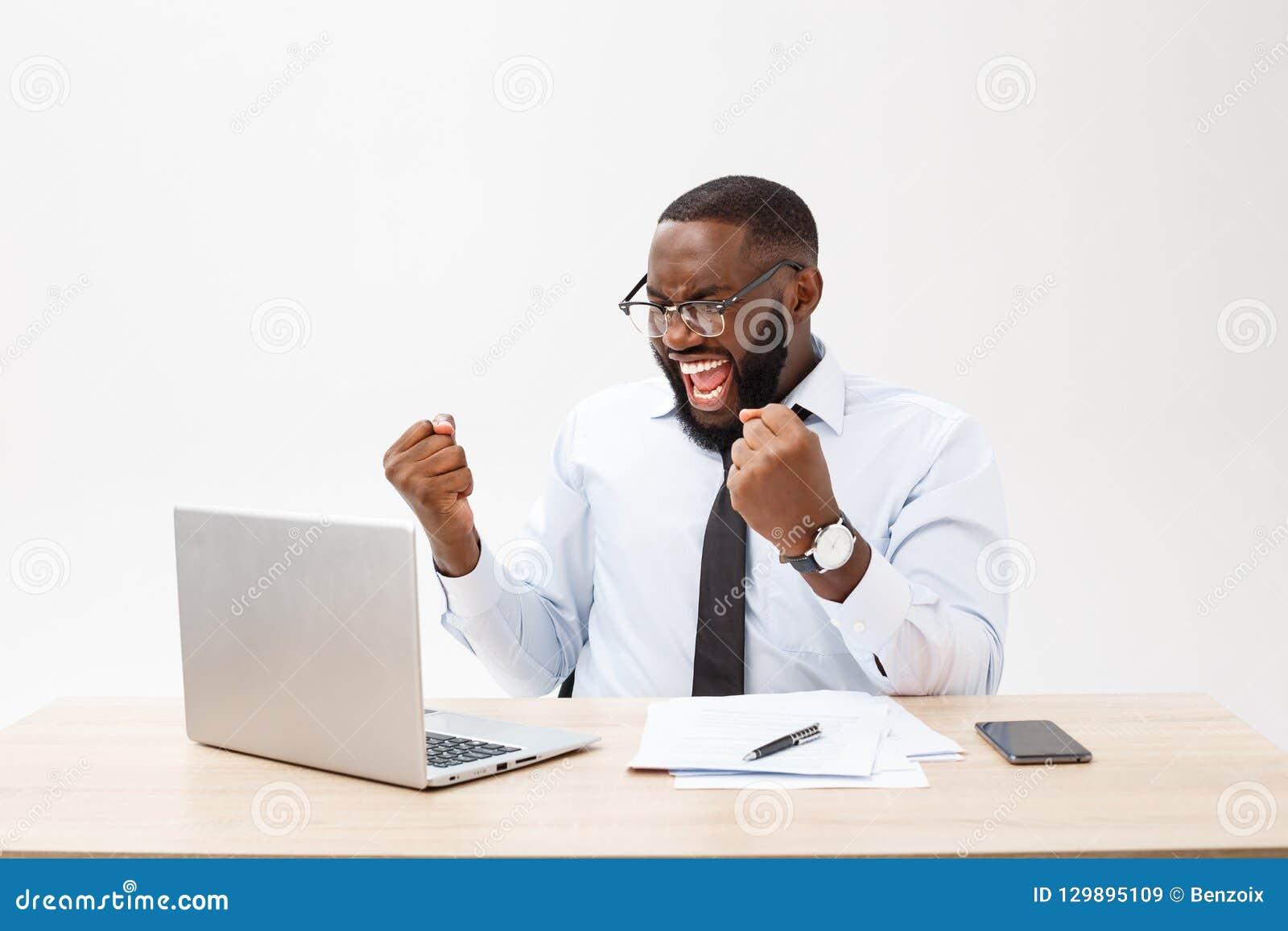 O negócio é sua vida Homem africano novo alegre no vestuário formal e no trabalho no portátil