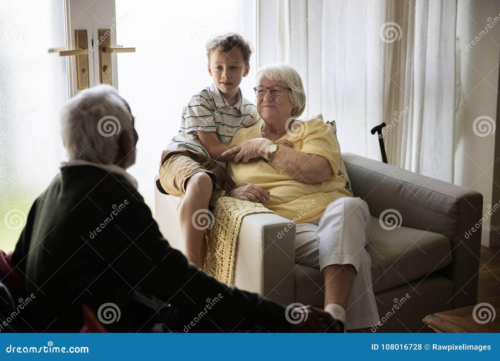 O neto está em uma sala de visitas com avós