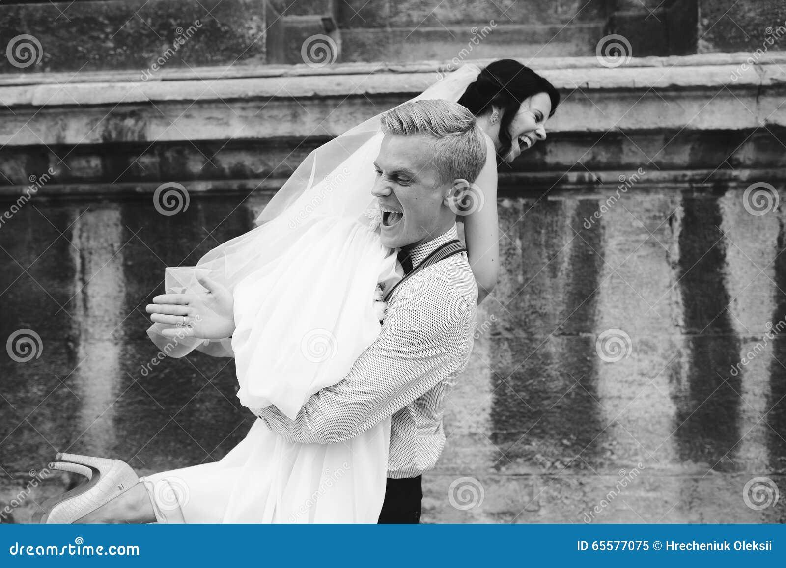 O noivo leva a noiva em seus braços
