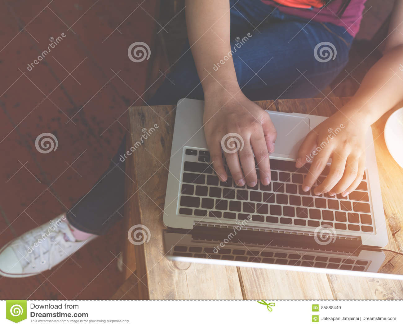 O ` novo bonito s da mulher do moderno entrega o trabalho ocupado em seu portátil que senta-se na tabela de madeira em uma cafeta