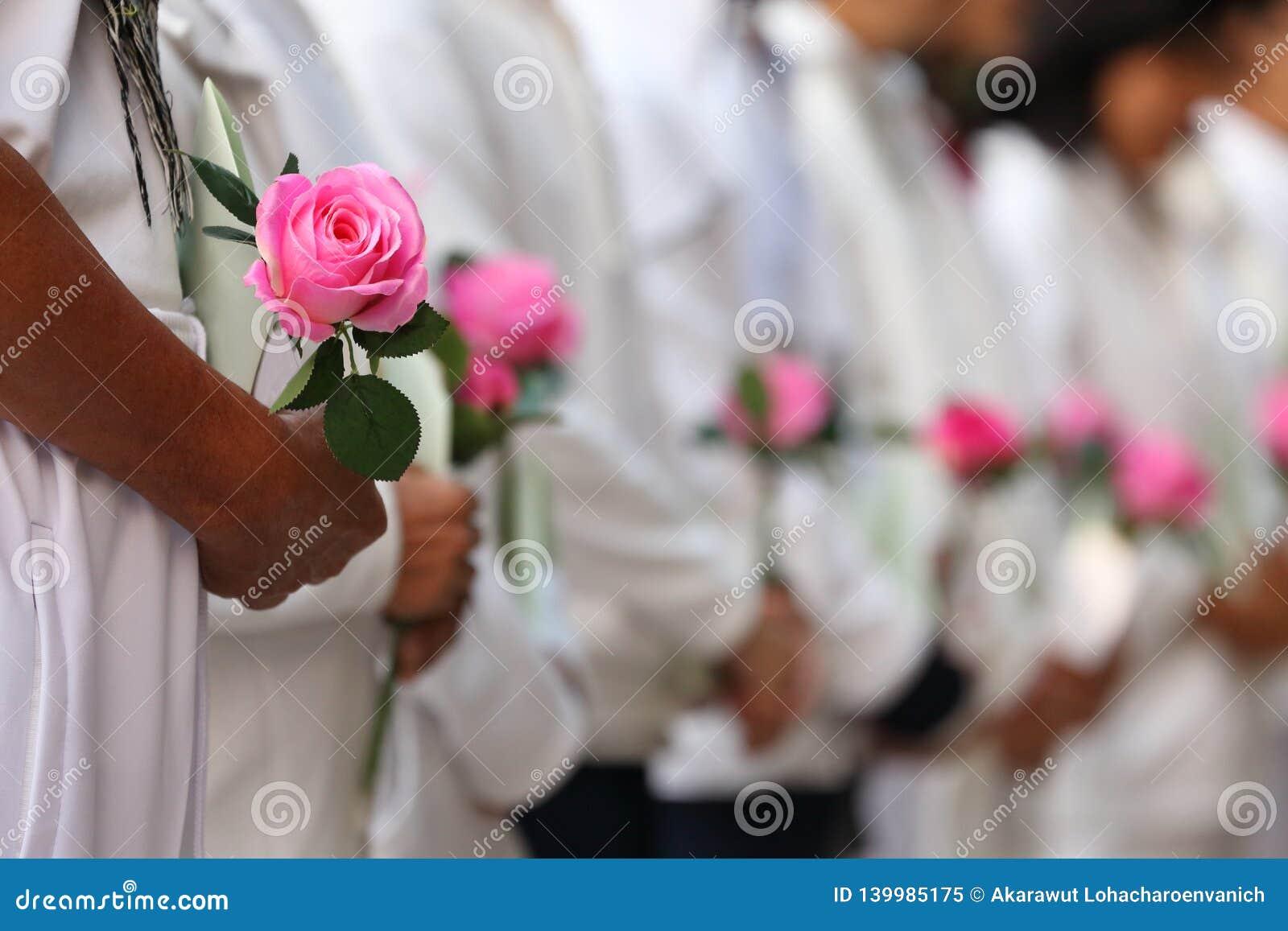 O oferecimento do grupo de pessoas aumentou flor que expressa os pêsames para respeitar o perdido do amor um durante a cerimônia