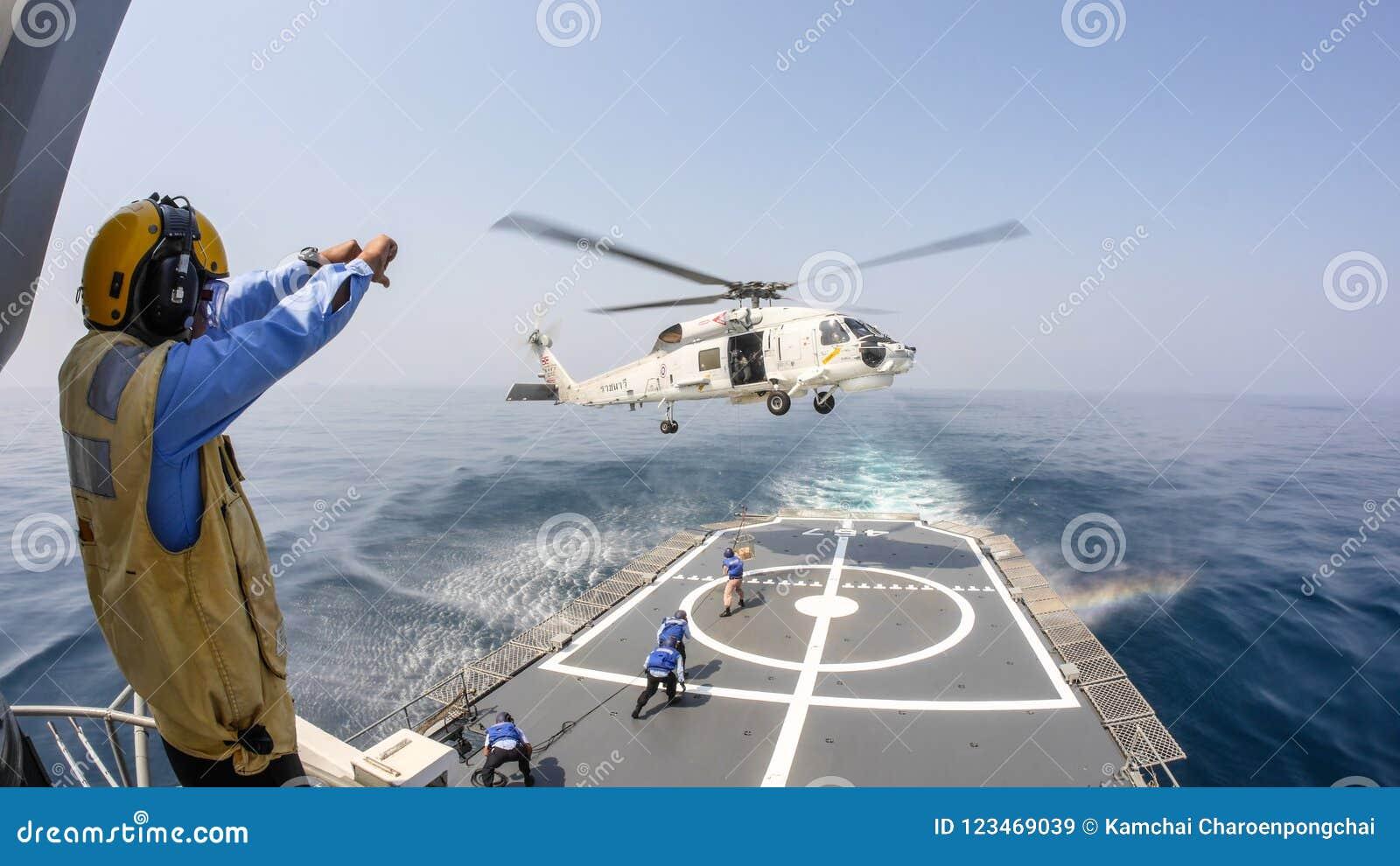 O oficial da plataforma de helicóptero dá o sinal de mão ao helicóptero do falcão do mar de Sikorsky S-70 que paira acima da plat