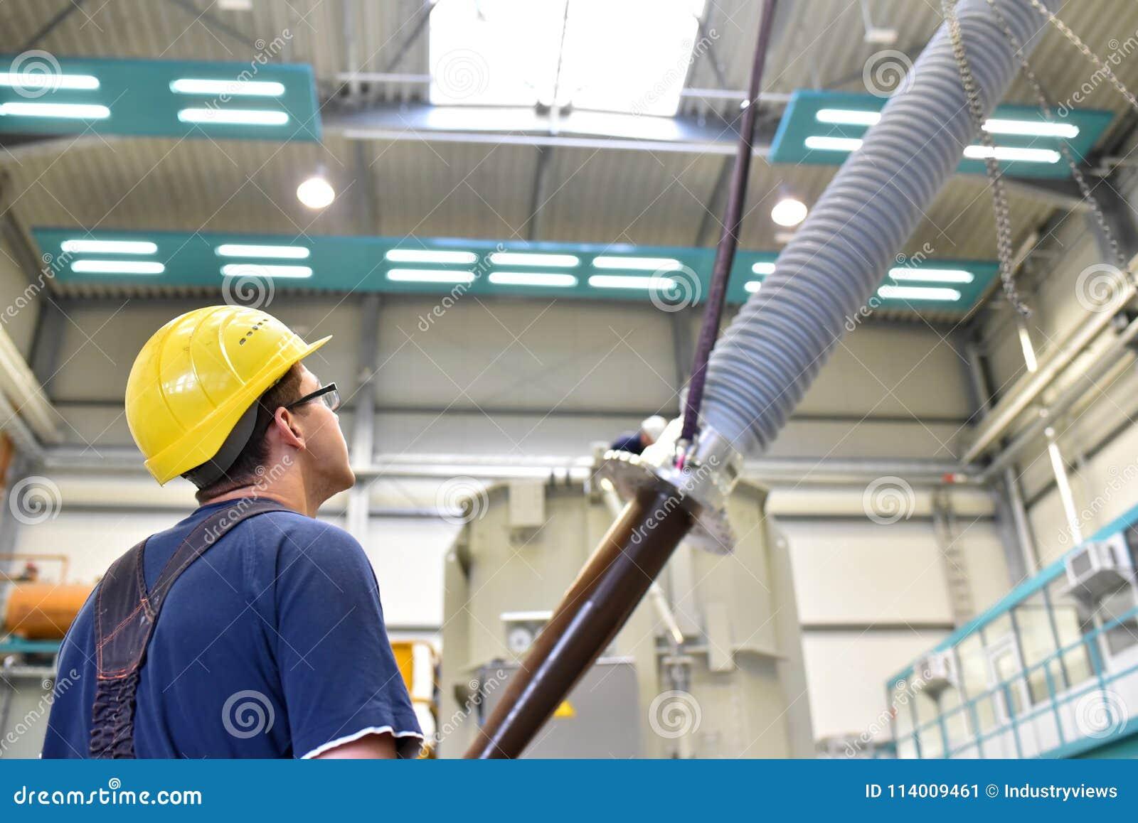 O operador instala um transformador em uma planta industrial em mechan