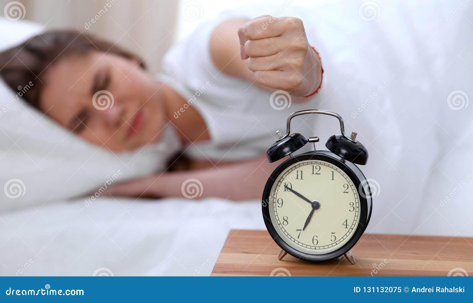 O oposto do despertador da jovem mulher sonolento que estica a mão a querer de soada do alarme desliga-o Acorde cedo, não