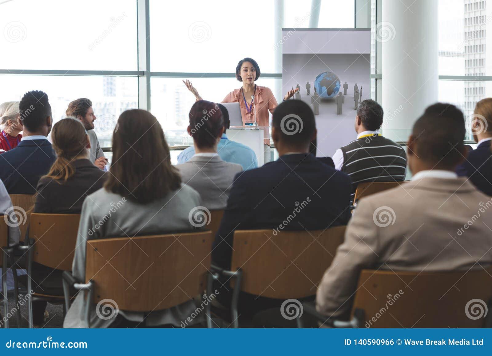 O orador fêmea com portátil fala em um seminário do negócio
