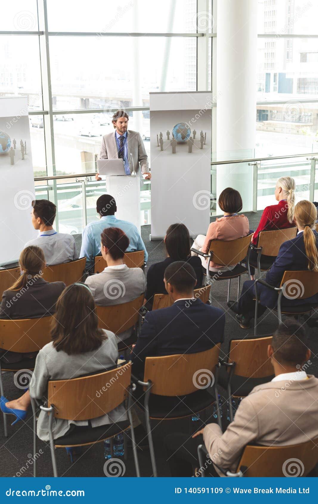 O orador masculino com portátil fala em um seminário do negócio