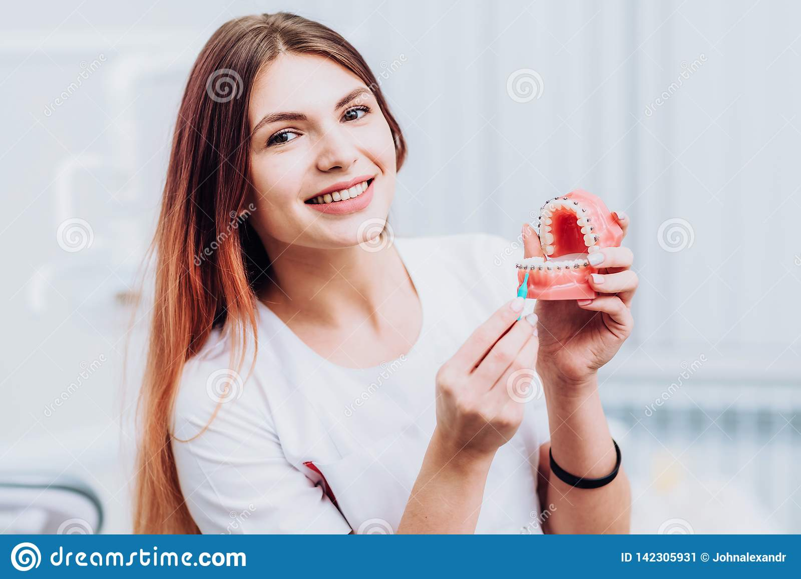 O orthodontist bonito do doutor mostra-lhe como importar-se com seus dentes