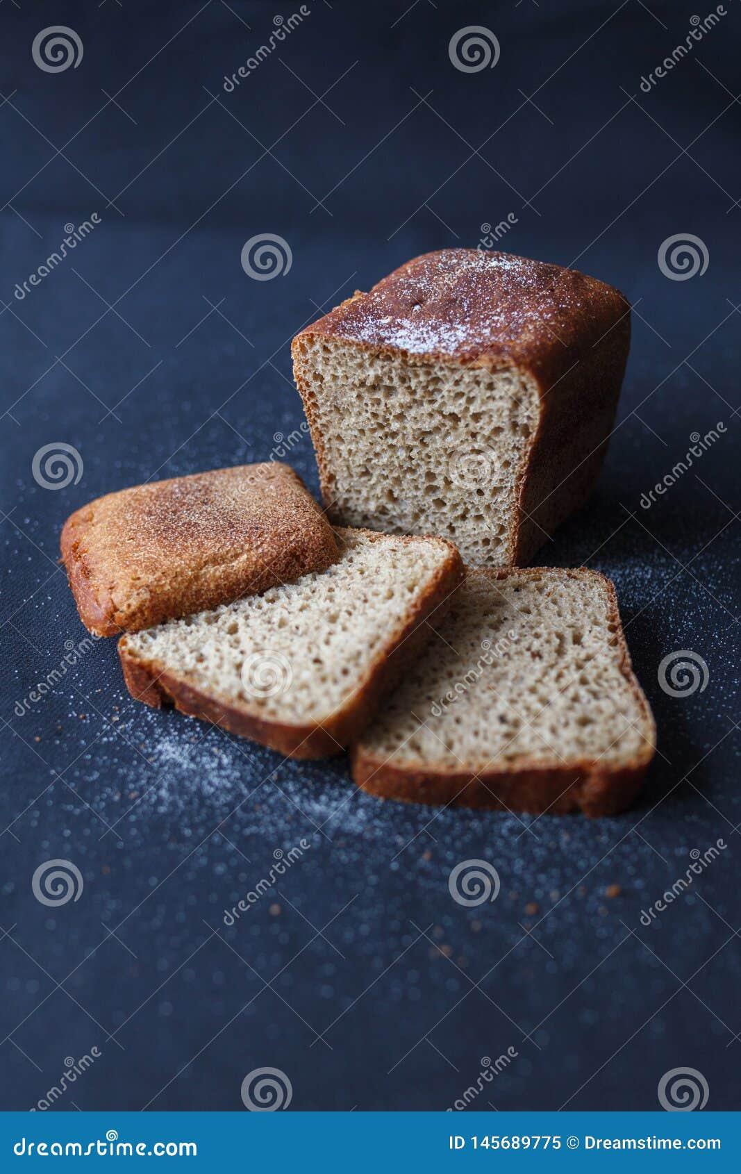 O pão, ícone da padaria, cortou o fundo isolado do onblack do pão integral fresco