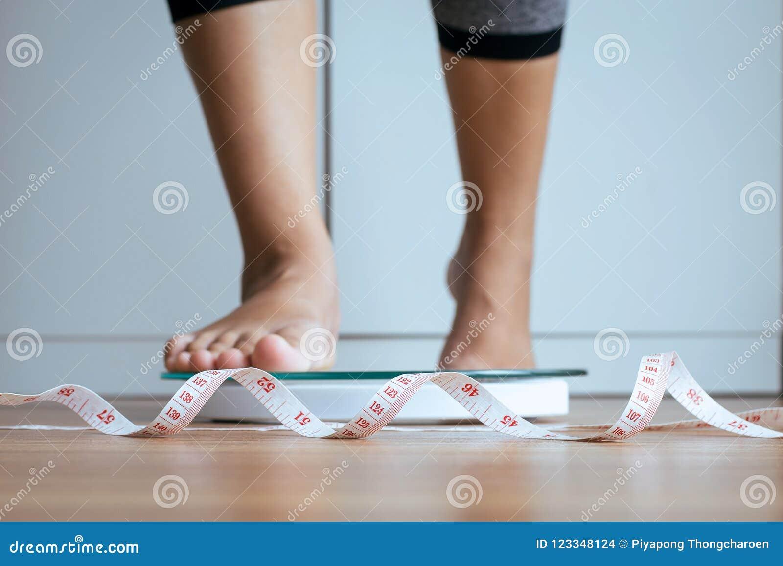 O pé da mulher que pisa sobre pesa escalas com fita métrica no primeiro plano, na perda de peso, no corpo e no conceito da boa sa