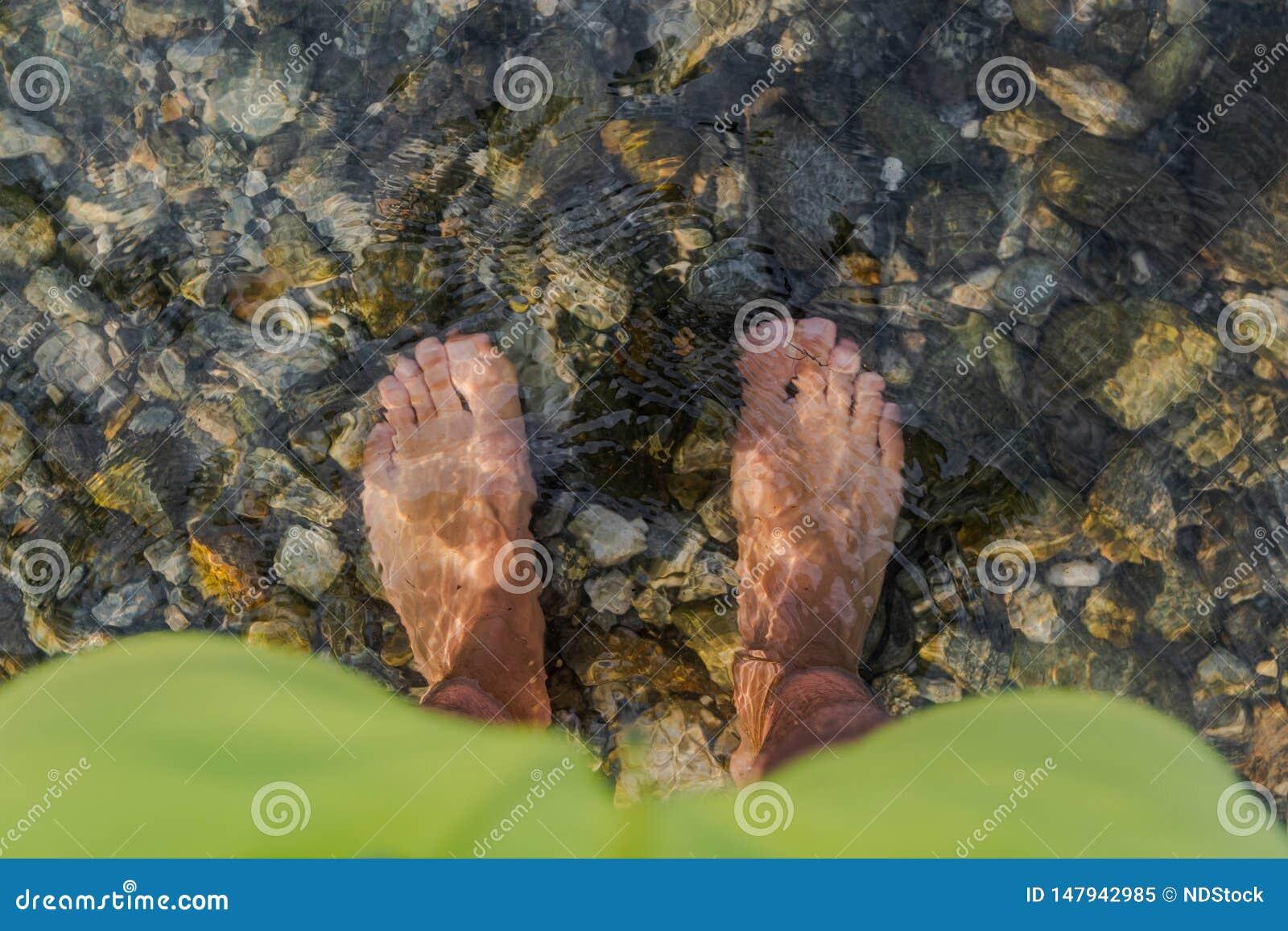 O pé do homem na água clara fria no maggiore do lago