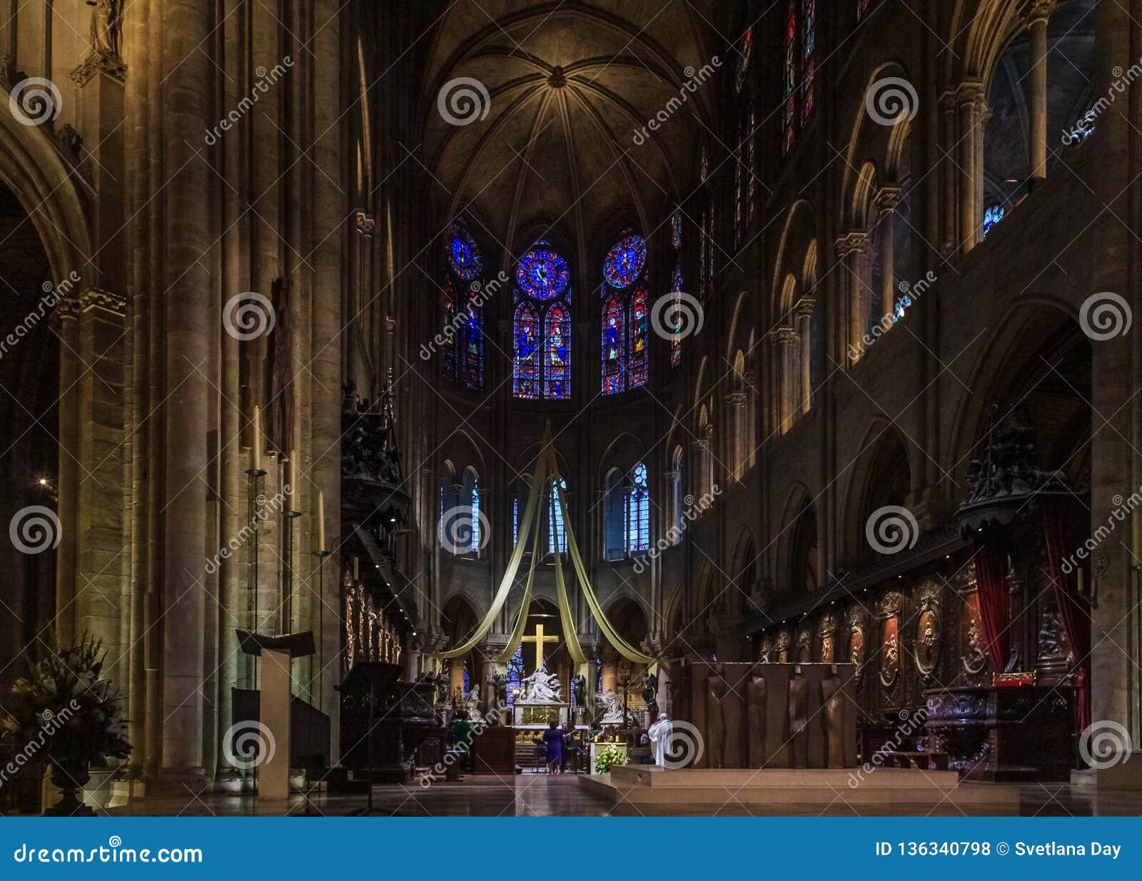 O púlpito, o altar e a cruz do Notre Dame de Paris Cathedral com as janelas de vitral ao longo da parede traseira dentro