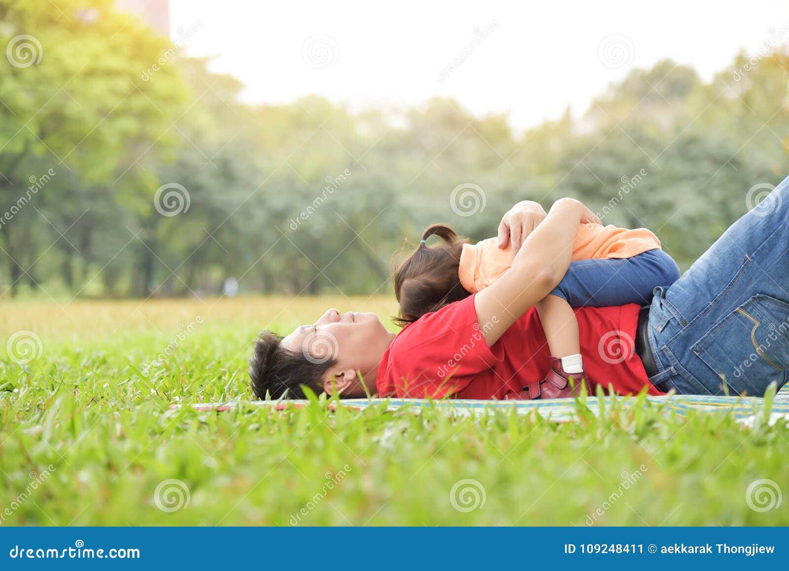 O pai asiático novo feliz e sua filha estão abraçando junto a