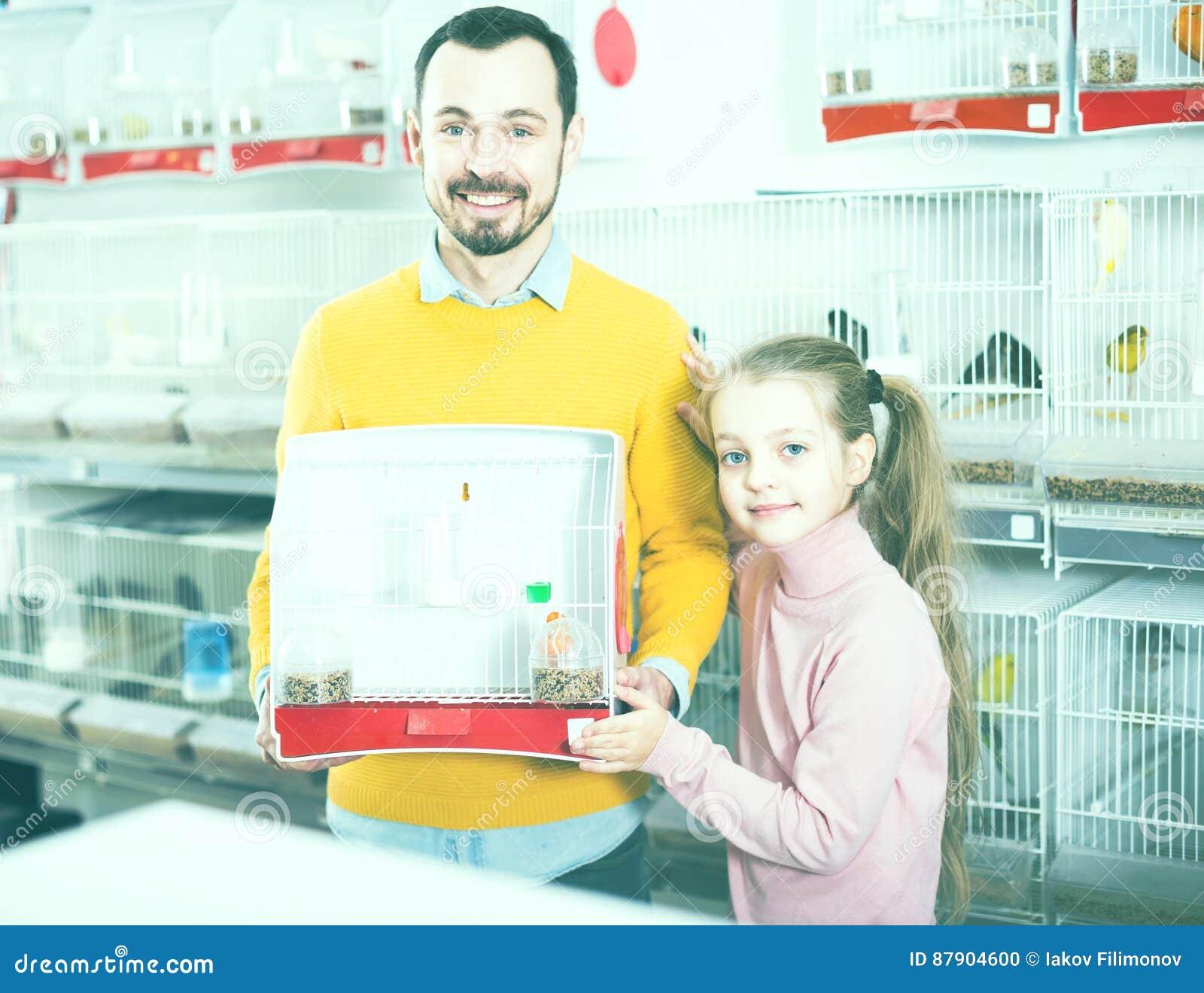 O pai com menina adquiriu a gaiola do canário e de pássaro