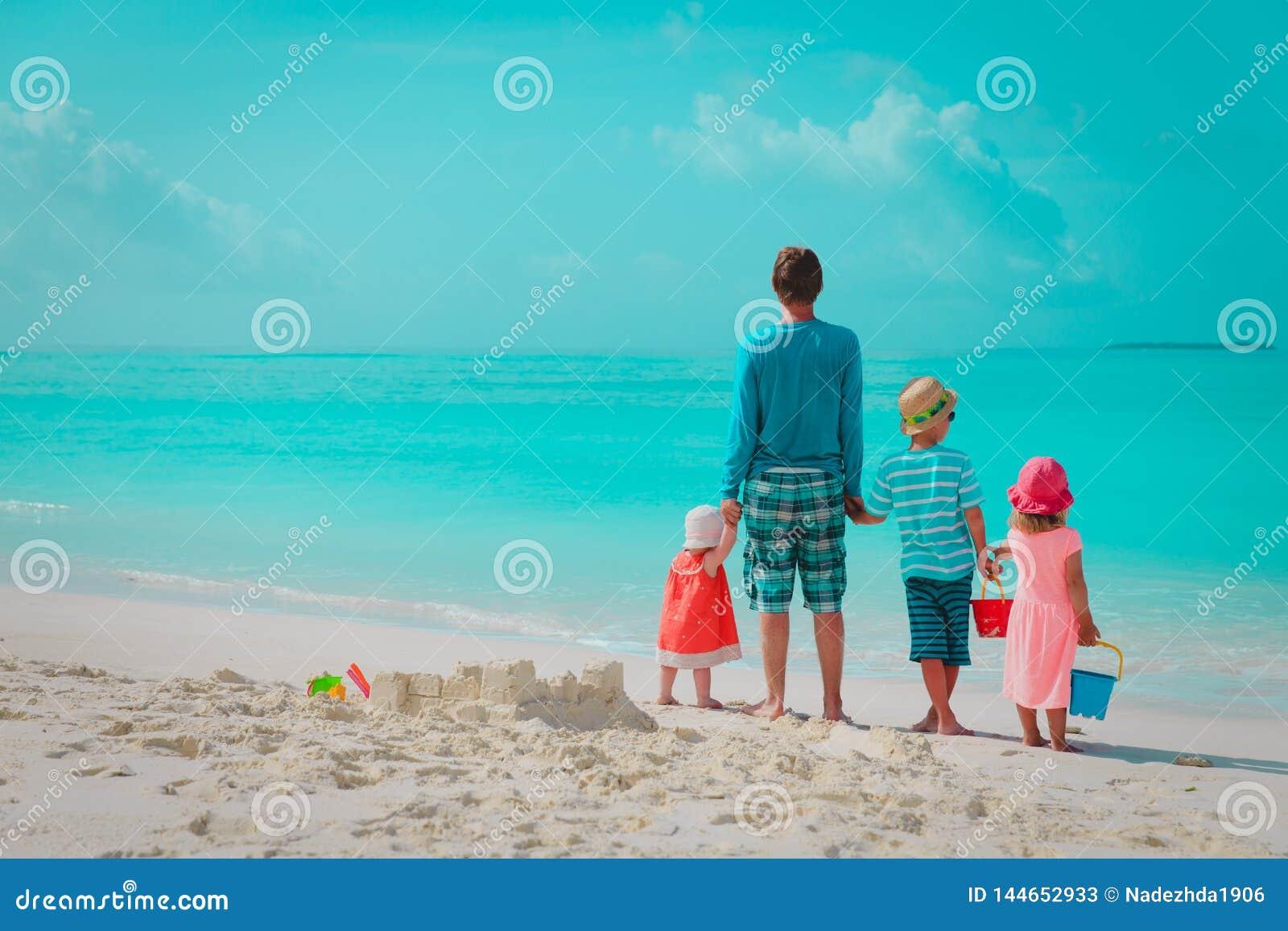 O pai com três crianças joga na praia, família no mar