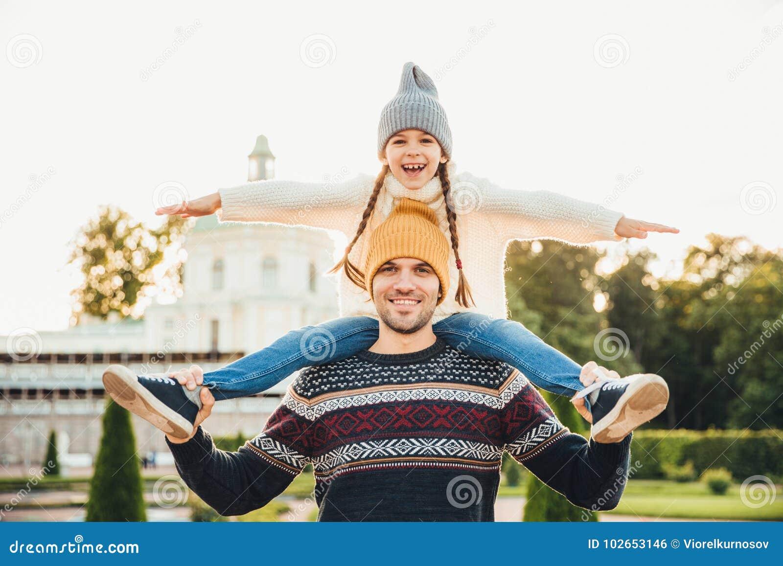 O pai considerável novo dá o reboque a sua filha de sorriso pequena, tem o divertimento junto quando tenha a excursão A criança p