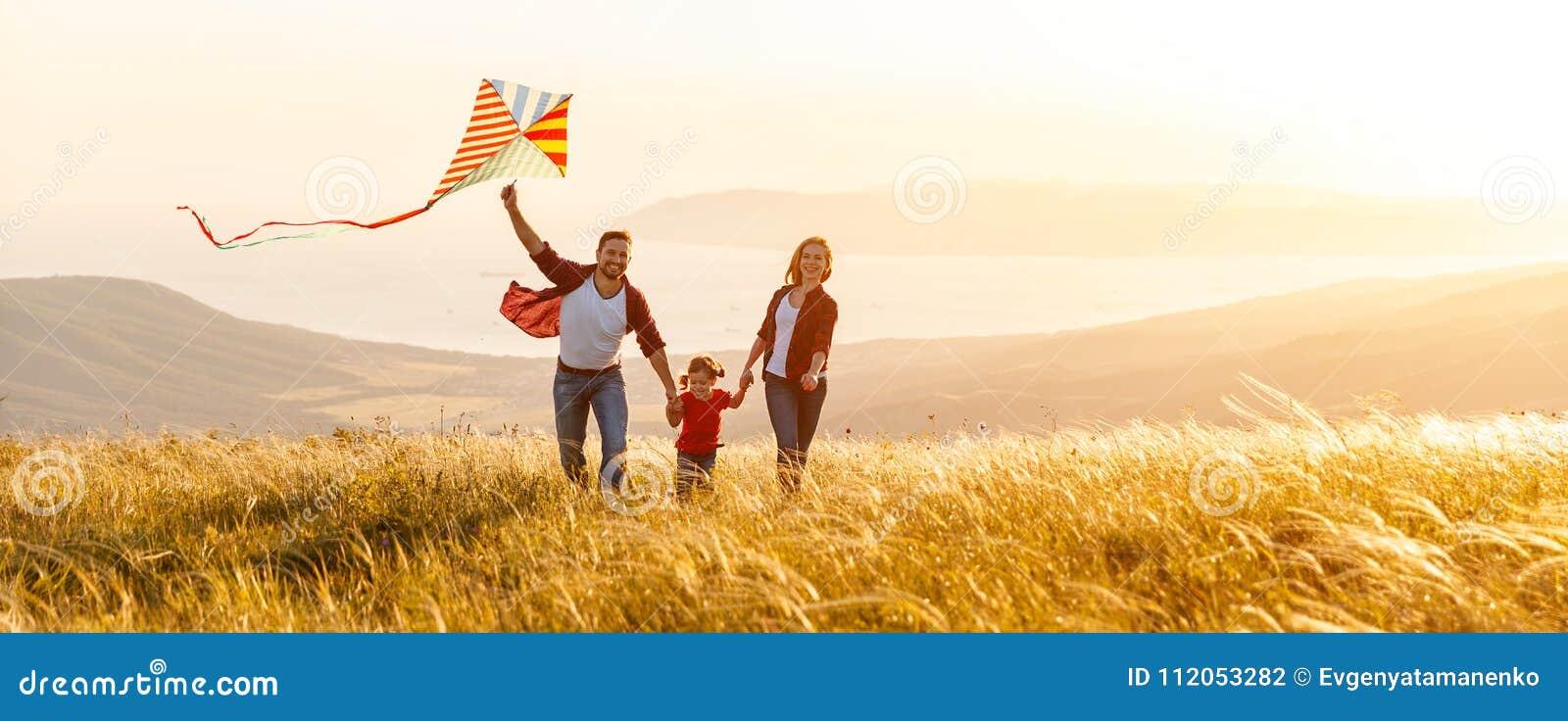 O pai da família, a mãe e a filha felizes da criança lançam um papagaio sobre