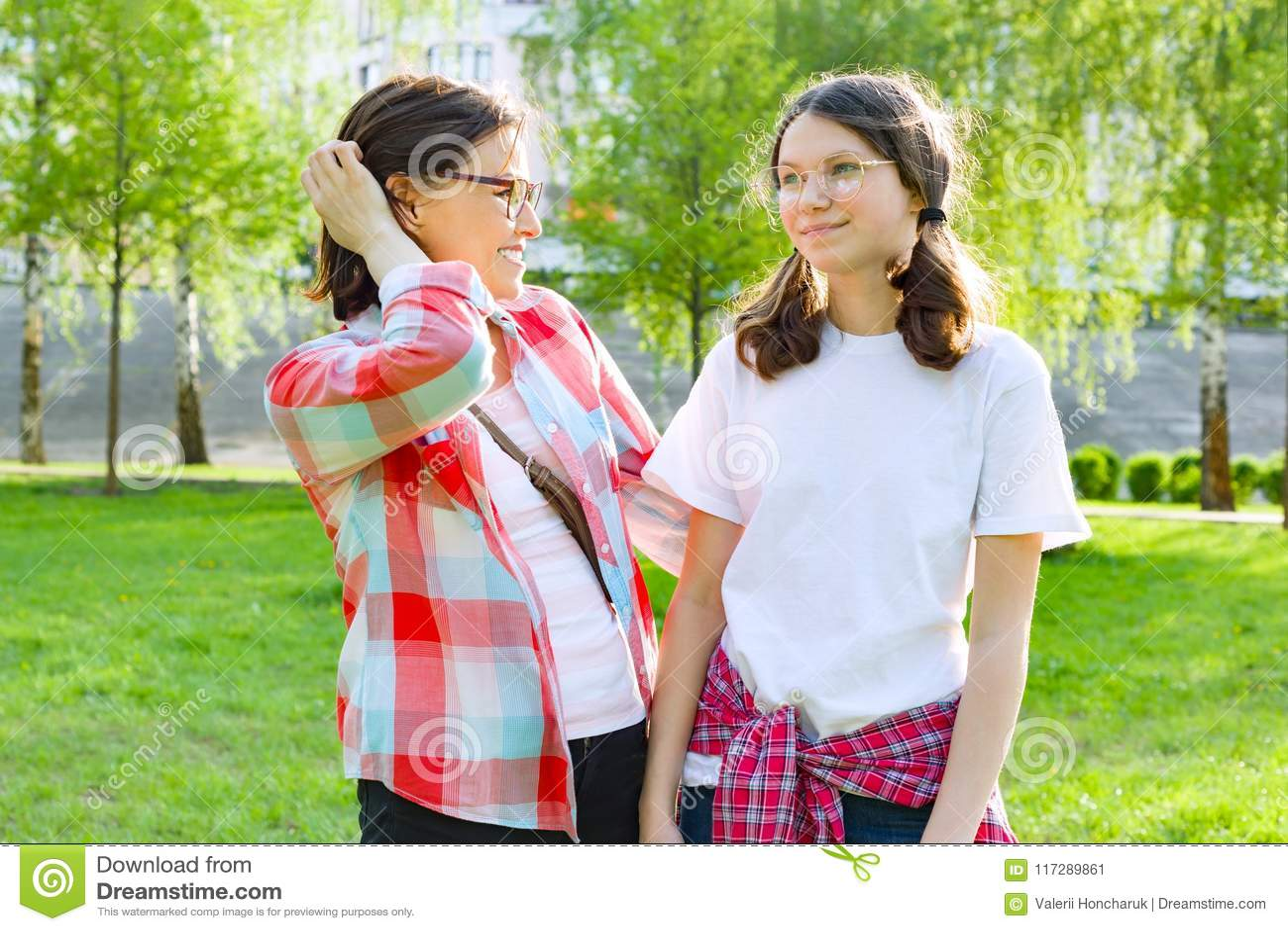 O pai e o adolescente, mãe falam com sua filha adolescente 13, 14 anos velhos Natureza do fundo, parque