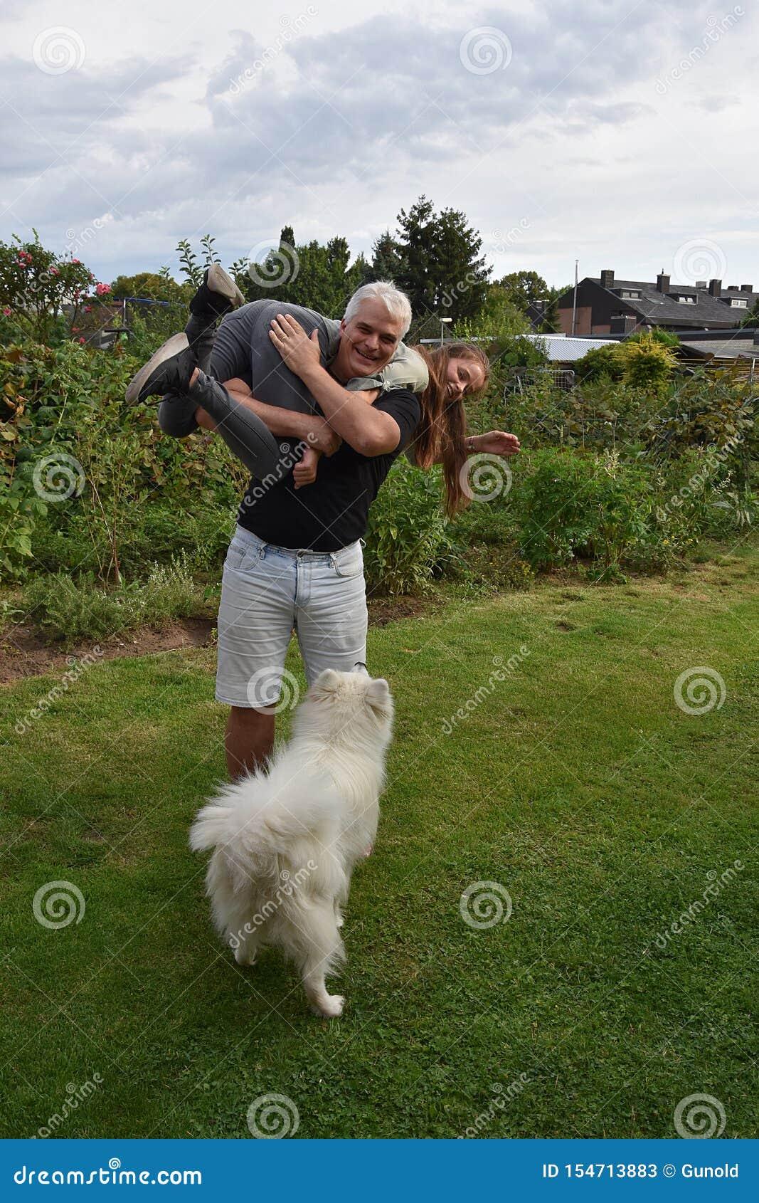 O pai e a filha discutindo, o cão olham surpreendido