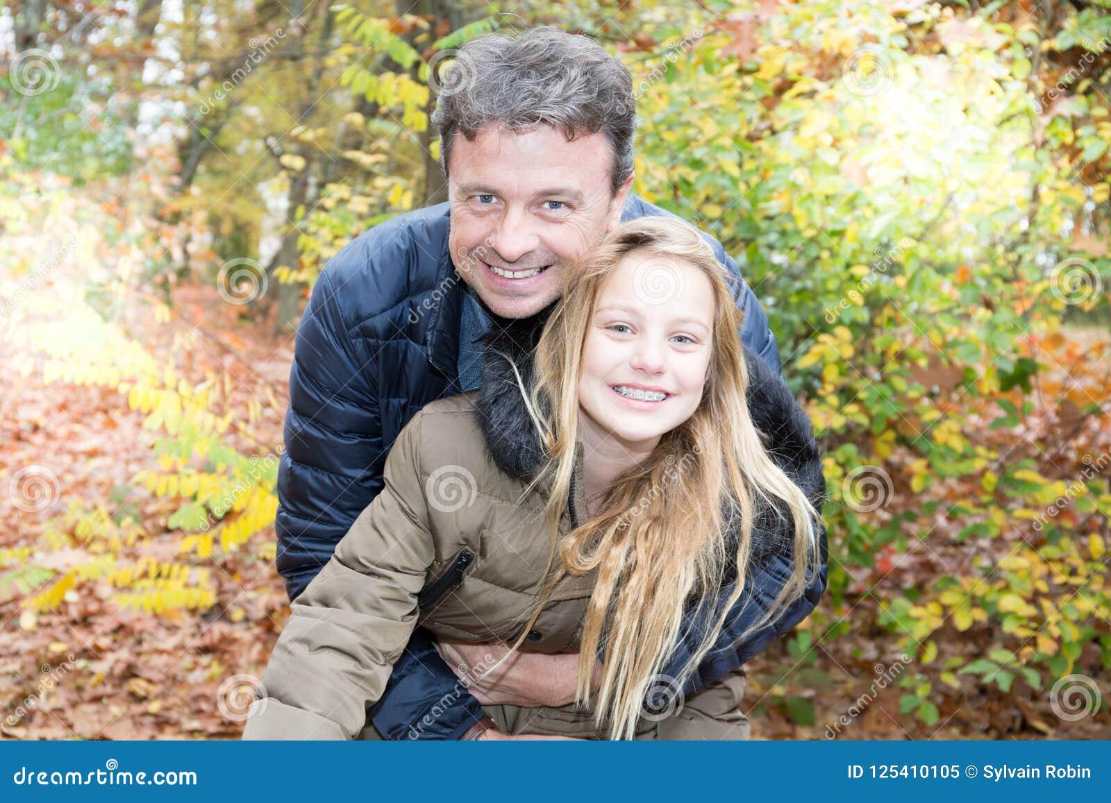 O pai e a filha no outono estacionam o jogo que riem a menina loura bonita abraçam seu paizinho
