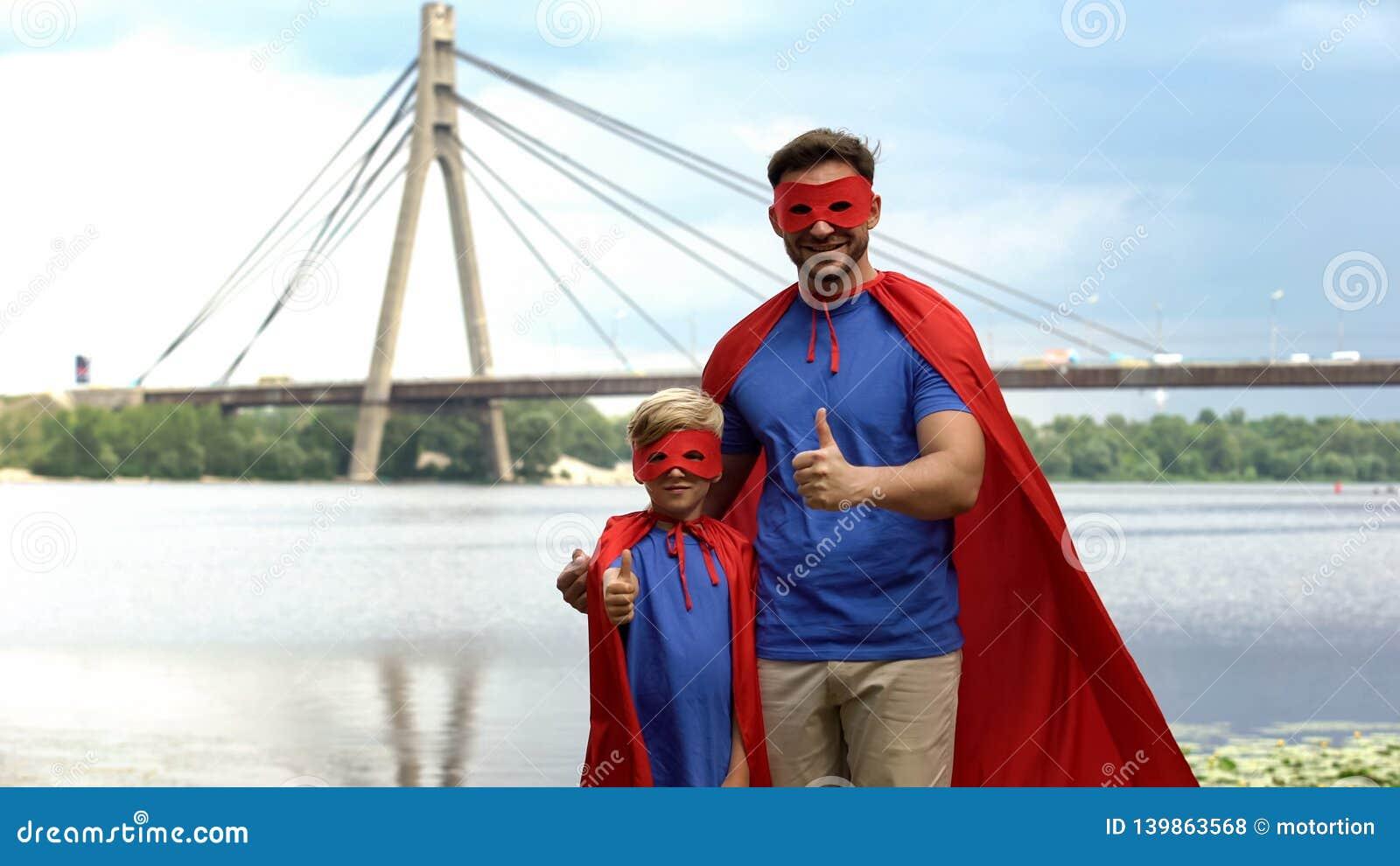 O pai e o filho no super-herói trajam mostrar os polegares acima, a motivação e os trabalhos de equipa