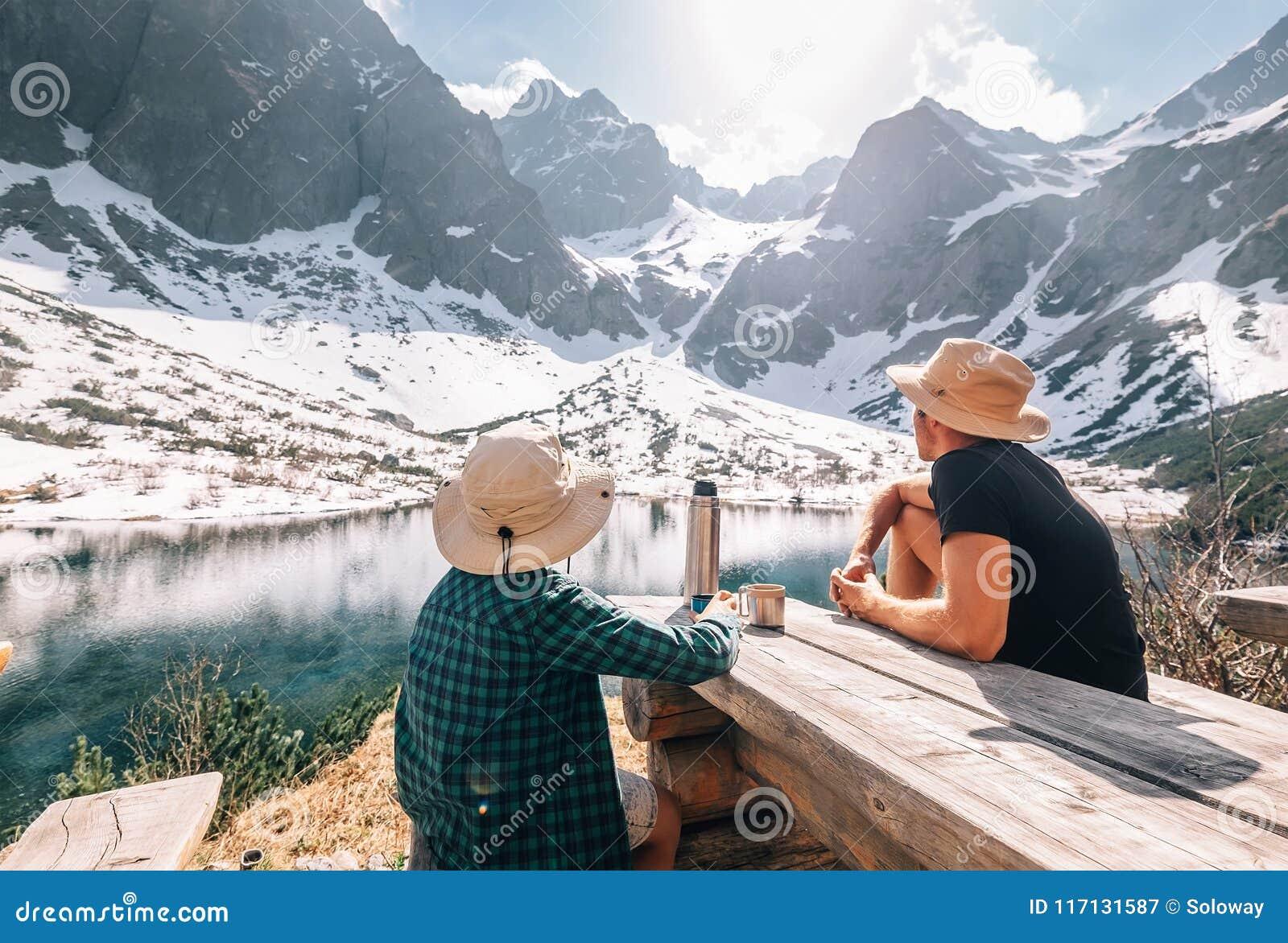 O pai e o filho que caminham o viajante descansam e bebem o chá perto da montagem