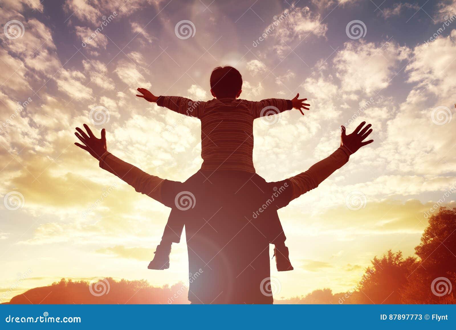 O pai e o filho do tempo da família olham o por do sol