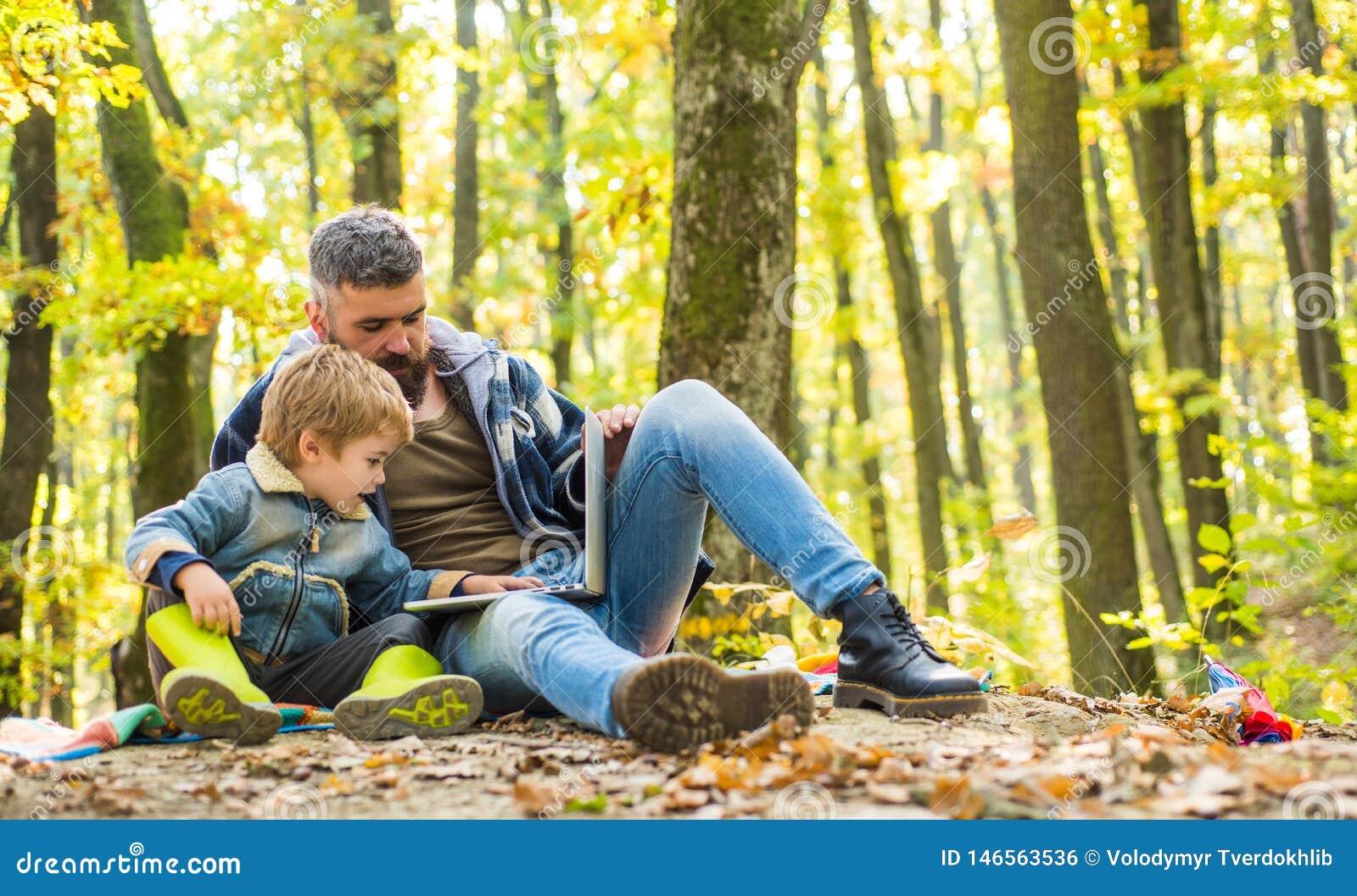 O pai ensina a uso do filho a tecnologia moderna Unido com a natureza Lição da ecologia Escola da floresta e educação da ecologia