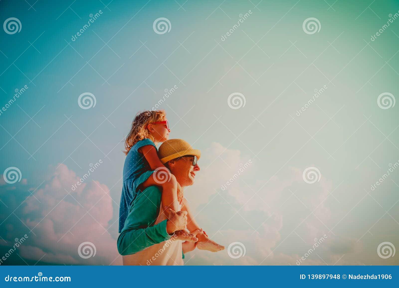 O pai feliz e a filha pequena jogam no céu
