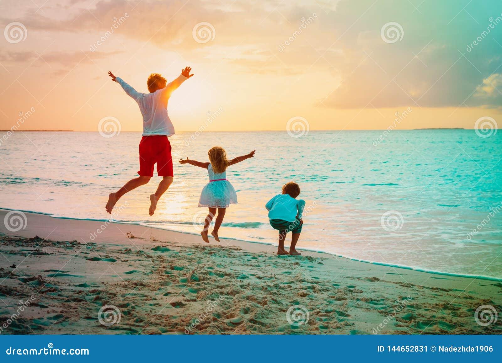 O pai feliz murcha o jogo da filha e do filho na praia