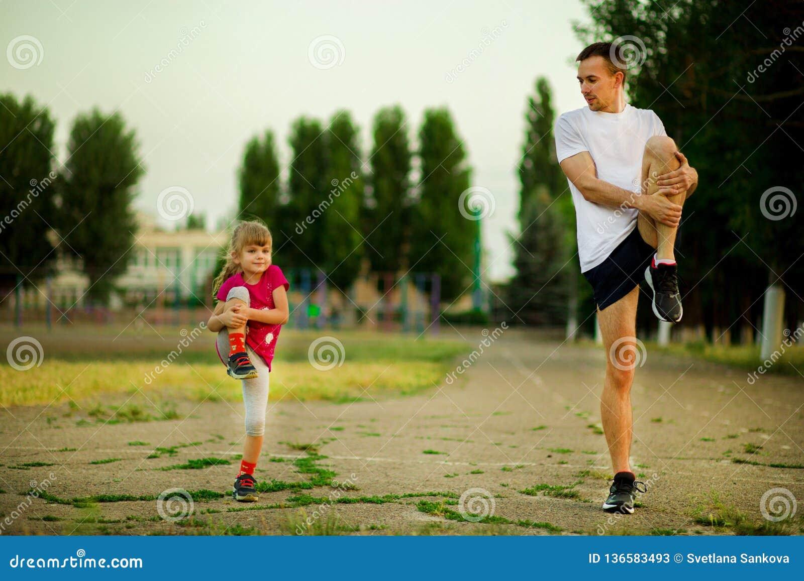 O pai novo atlético e a filha pequena fazem exercícios no estádio