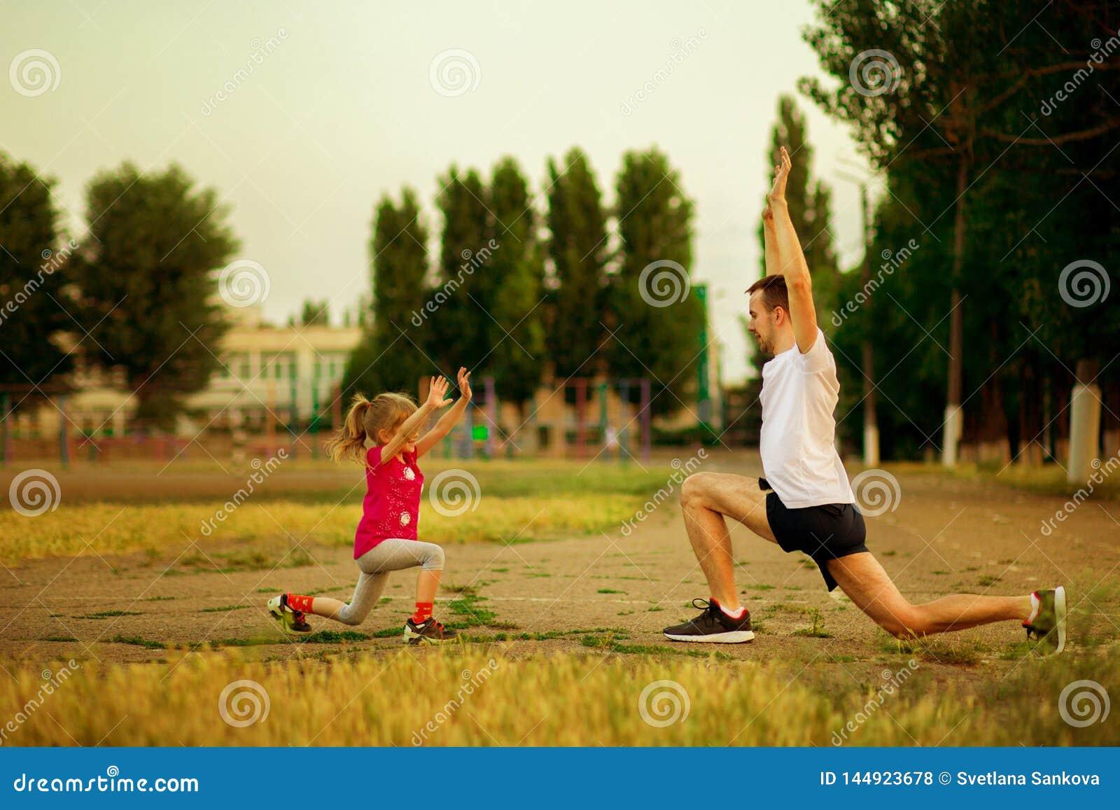 O pai novo atl?tico e a filha pequena fazem exerc?cios no est?dio