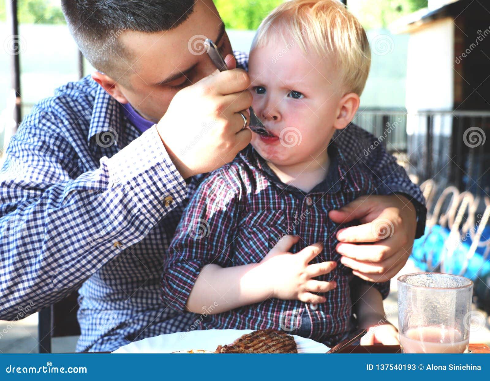 O paizinho alimenta a criança em um café