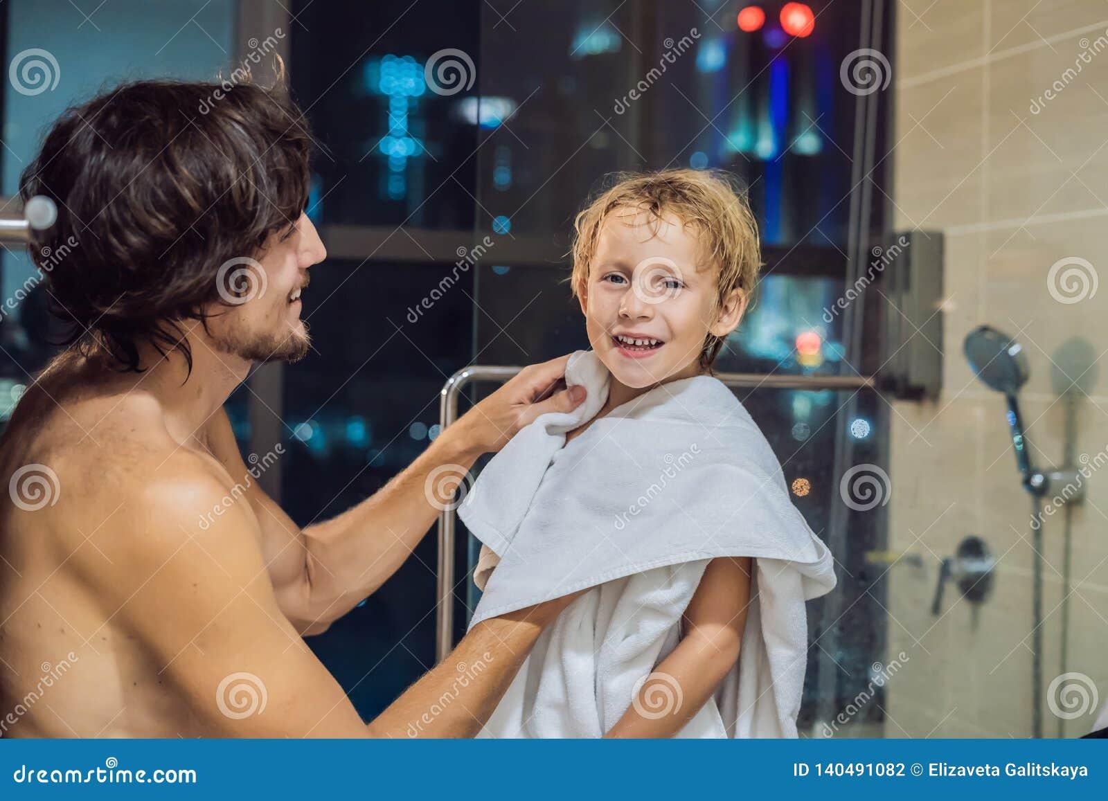 O paizinho limpa seu filho com uma toalha após um chuveiro na noite antes de ir dormir no fundo de uma janela com a