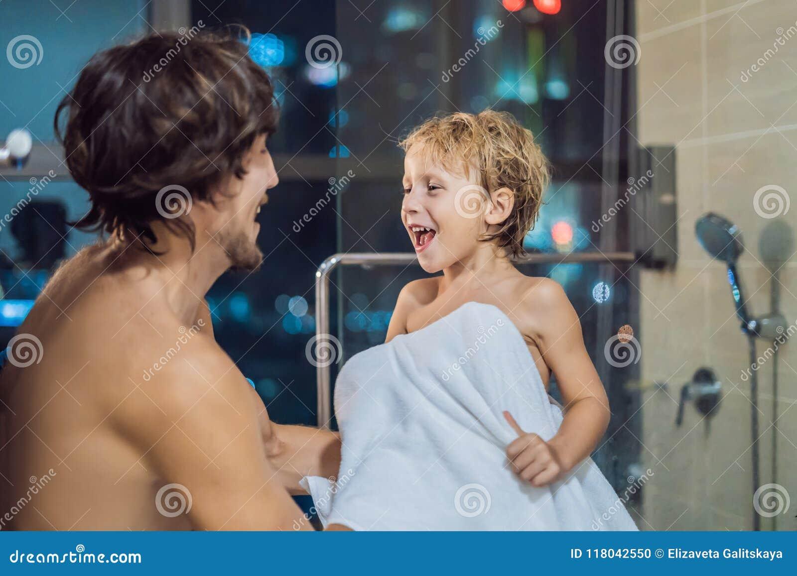 O paizinho limpa seu filho com uma toalha após um chuveiro no bef de nivelamento