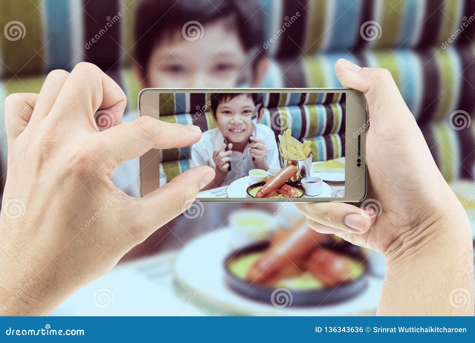 O paizinho toma a foto móvel do menino asiático que come batatas fritas