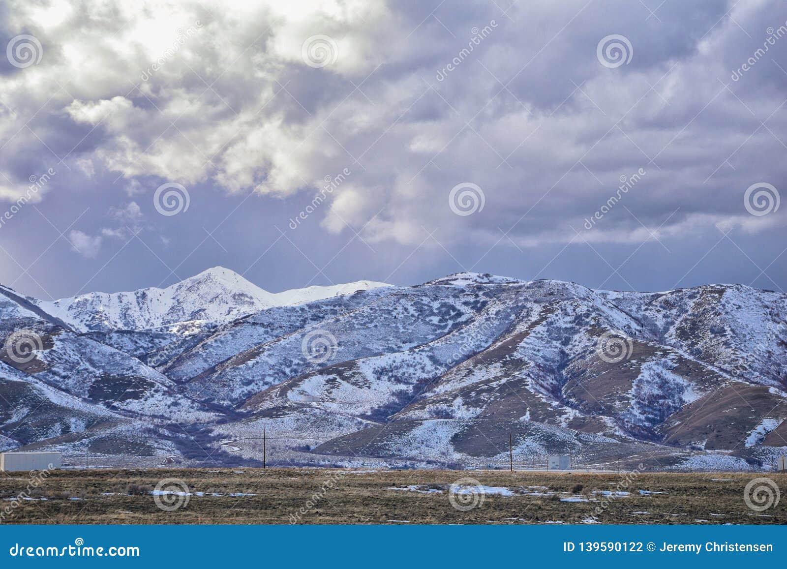 O panorama do inverno da neve da cordilheira de Oquirrh tampou, que inclui a mina de Bingham Canyon Mine ou de cobre de Kennecott