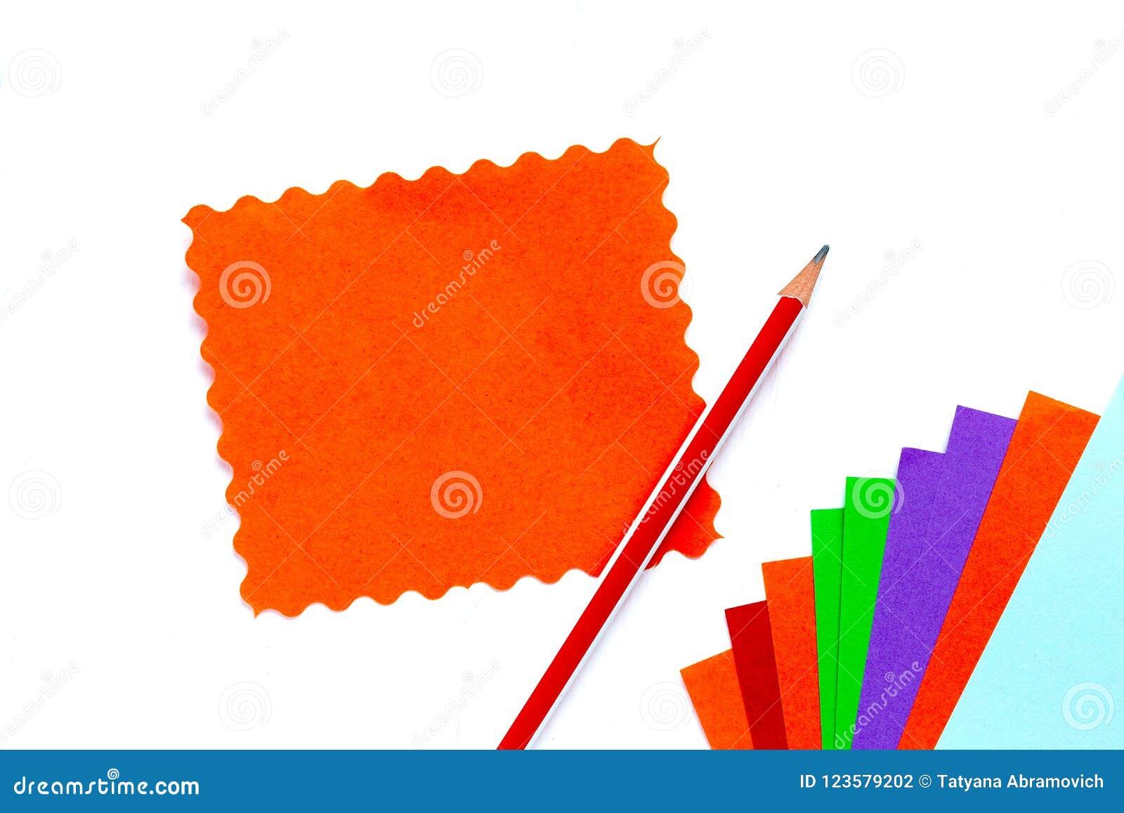 O papel da cor para o origâmi encontra-se com um fã, uma folha de papel alaranjada com uma borda ondulada, um lápis molde