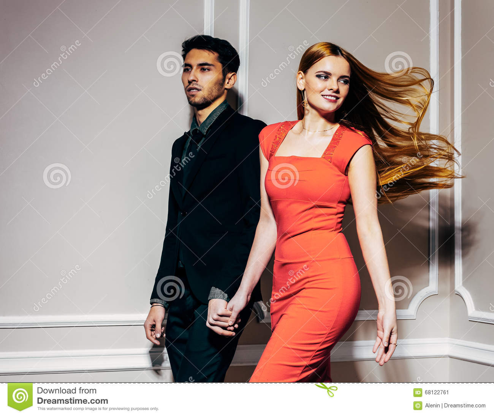 O par bonito novo da forma está movendo-se rapidamente A menina é cabelo vermelho bonito longo de vibração Guarde as mãos indoor